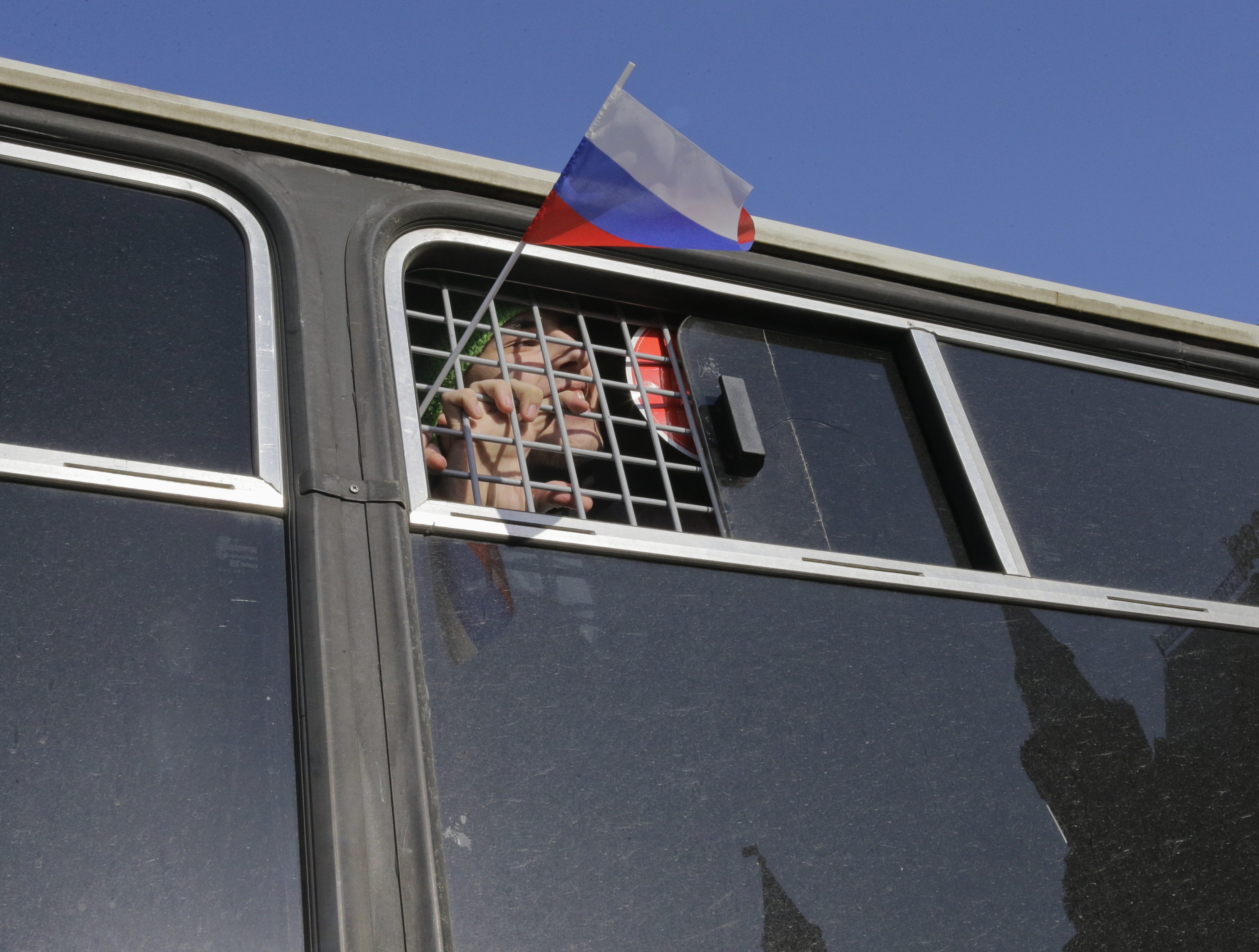 A participant waves a flag from a police bus after being detained at a rally to protest the sentencing of anti-corruption blogger and opposition leader Alexei Navalny, in Moscow March 1, 2014. A Russian court placed Navalny under house arrest for at least two months on Friday and barred him from using the Internet or speaking to the media.
