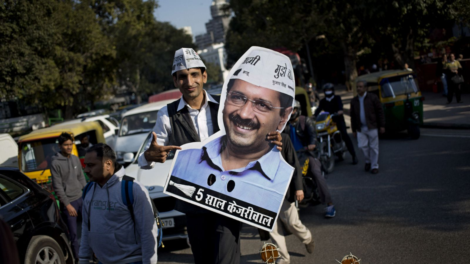 "A supporter of Aam Aadmi Party, or Common Man Party, holds a cut-out of party leader Arvind Kejriwal on the last day of campaigning for Delhi state elections in New Delhi, India, Thursday, Feb. 5, 2015. Delhi will go to the polls on Feb. 7. Writing reads ""5 years Kejriwal,"" referring to the 5 year term for Indian lawmakers."
