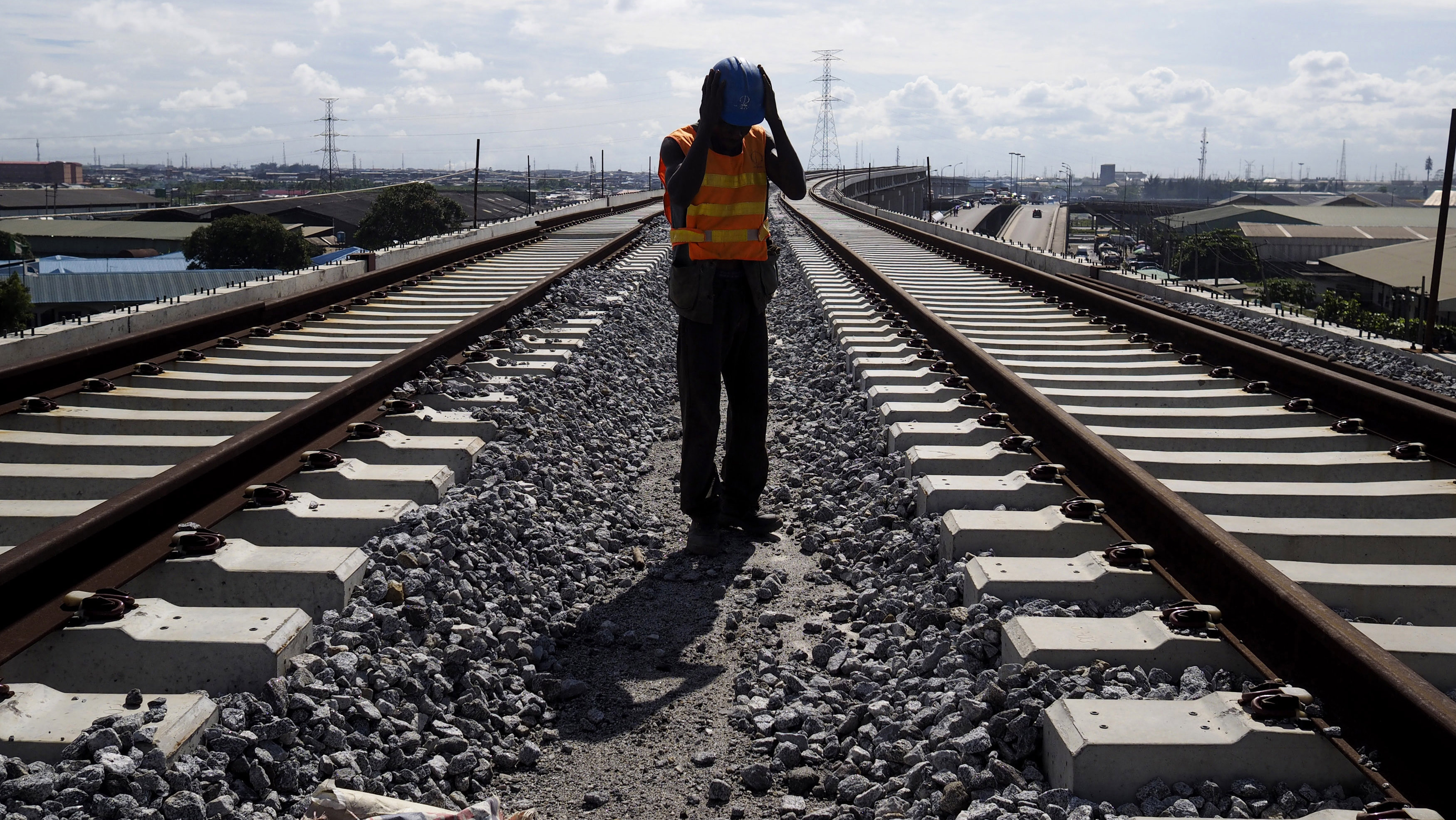 A worker adjusts his hard hat at the National Arts Theatre stop of the light rail system under construction in Lagos, Nigeria, May 30, 2014. Started in 2009 to ease traffic, Lagos state government is building a rail system with the China Civil Engineering Construction Corporation. The first test runs should start in 2015, according to an official at the National Arts Theatre work site.