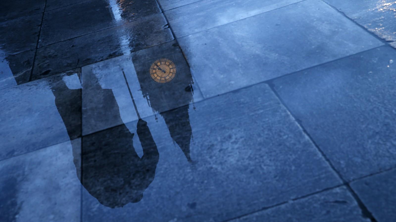 A rainy London street reflects Big Ben.