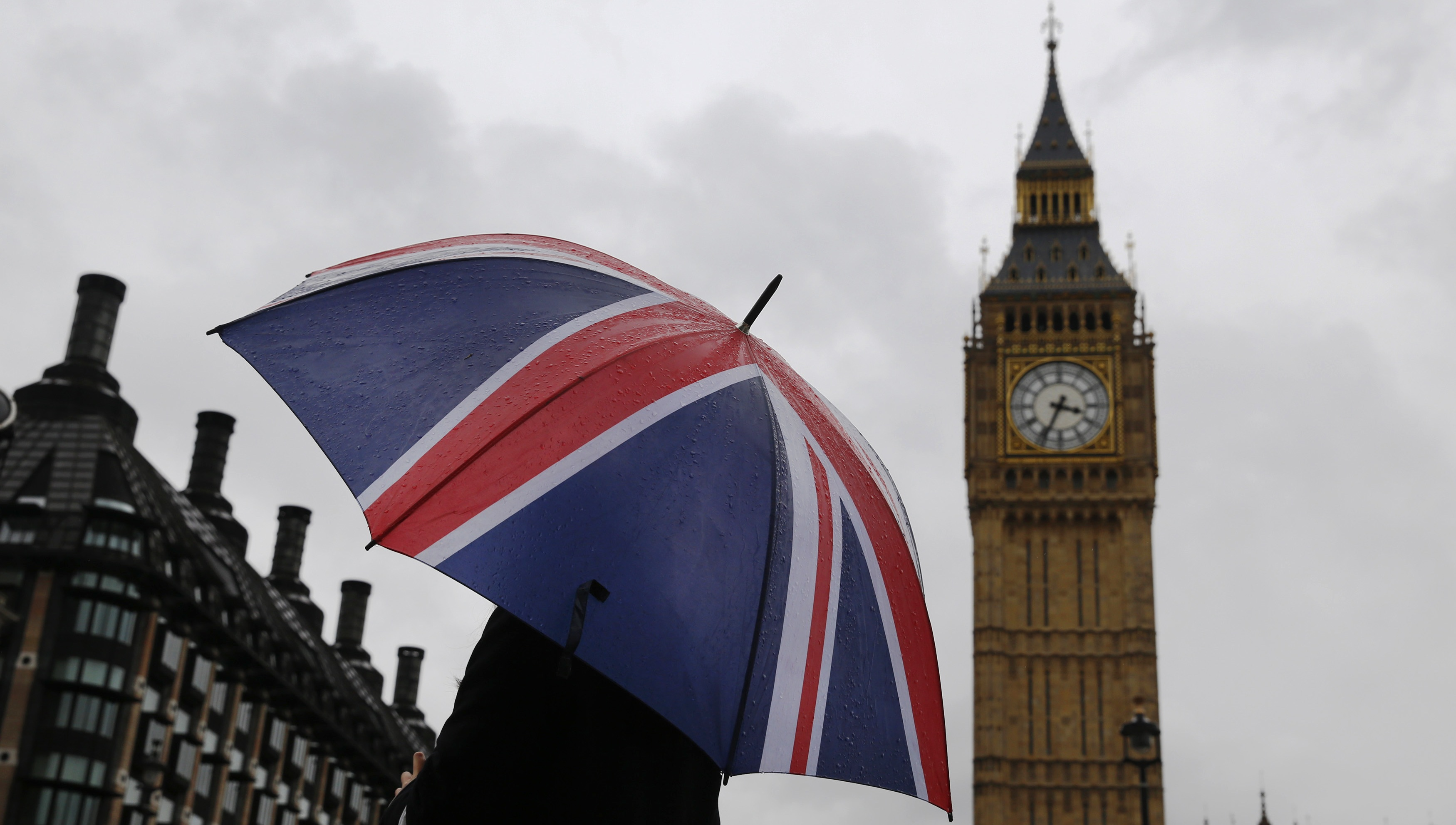 A woman holds a Union flag umbrella in front of the Big Ben clock tower (R) and the Houses of Parliament in London October 4, 2014. REUTERS/Luke MacGregor (BRITAIN - Tags: ENVIRONMENT CITYSCAPE TRAVEL)
