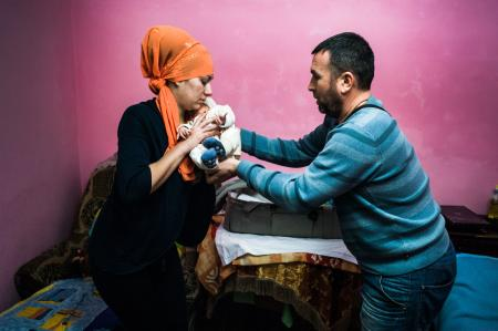 Suleiman performs a Muslim naming ceremony for a two-week old baby.