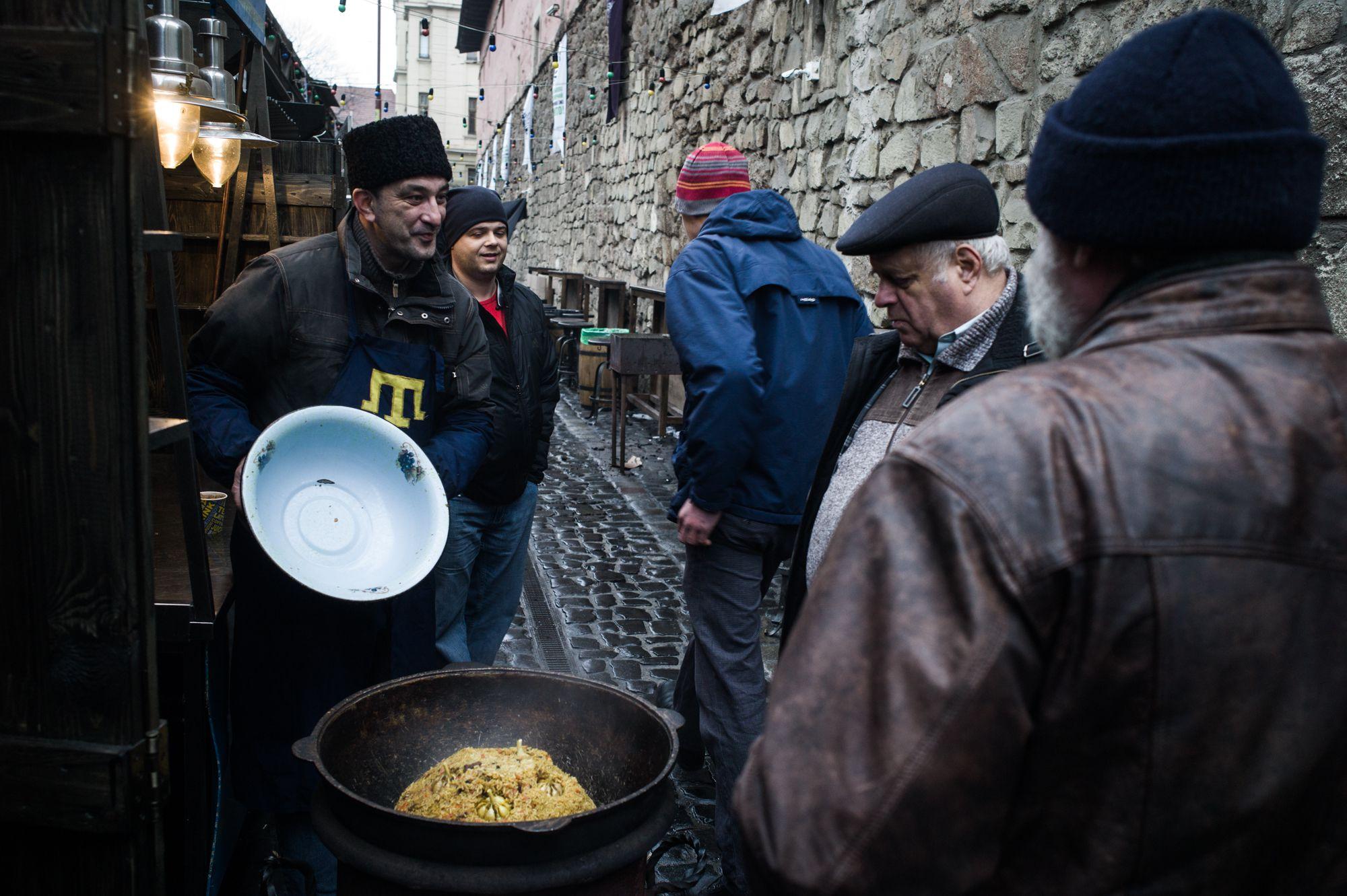 """Yashar selling Uzbek """"plov"""" in the market in Lviv."""