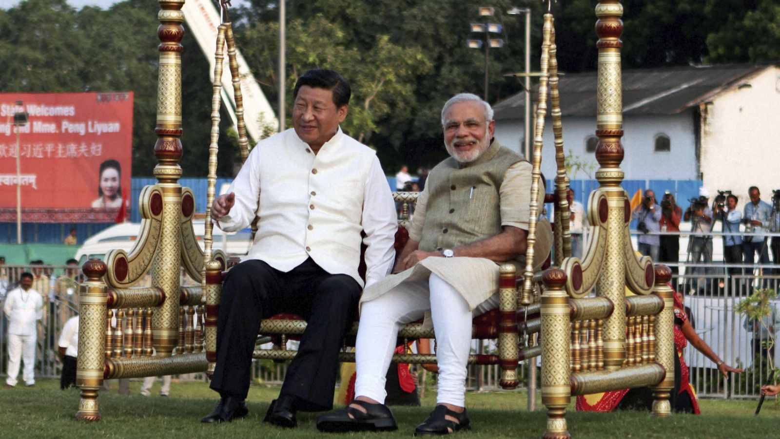 Chinese President Xi Jinping, left and Indian Prime Minister Narendra Modi, sit on a traditional swing at the Sabarmati River front in Ahmadabad, India, Wednesday, Sept. 17, 2014. Xi landed in the Indian prime minister's home state of Gujarat on Wednesday for a three-day visit expected to focus on India's need to improve worn out infrastructure and reduce its trade deficit.