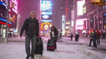 Alexander Valeur of Denmark and Katia Borredo from Mexico carry their baggage through a snowstorm in Times Square, New York early morning January 27, 2015. A life-threatening blizzard barreled into the U.S. Northeast, affecting up to 20 percent of Americans by making workers and students housebound, halting thousands of flights and prompting New York to ban cars from roads and halt subway trains. REUTERS/Adrees Latif (UNITED STATES - Tags: ENVIRONMENT TRAVEL)