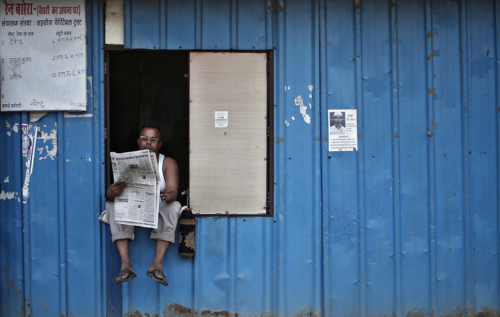 A man reads a newspaper as he sits on the window of a temporary shelter for homeless people in New Delhi.