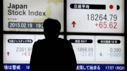 A man walks past an electronic board showing Japan's Nikkei average (top R) outside a brokerage in Tokyo February 19, 2015. Japanese stocks rose to a 15-year high on Thursday, helped by gains in financial stocks, while Sony Corp jumped on a well-received business plan. REUTERS/Toru Hanai (JAPAN - Tags: BUSINESS)