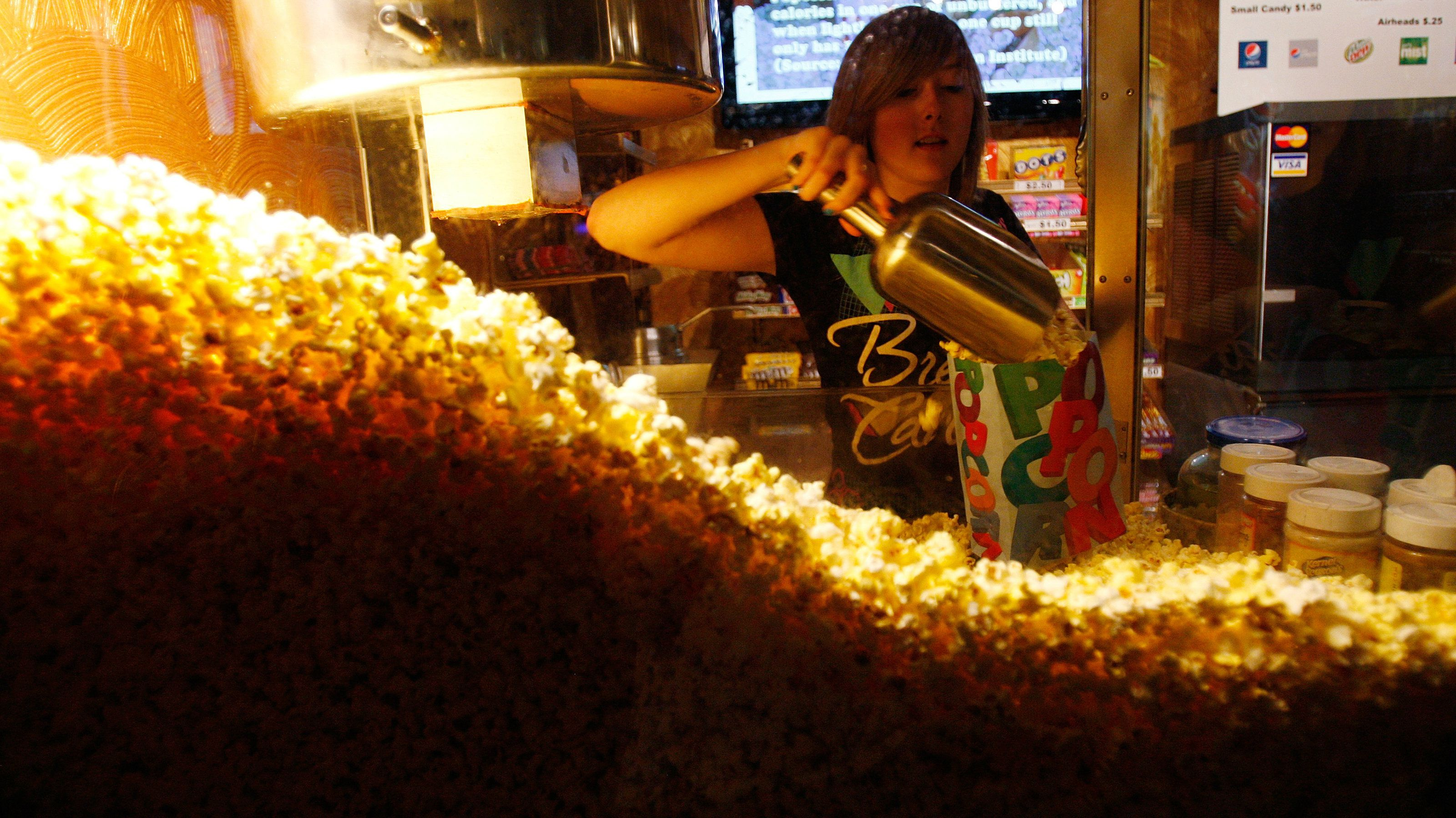 Cailynn Williams, 17, fills a bag of popcorn for a customer at the New Strand Theater in West Liberty, Iowa July 8, 2011. Todd Leach, who owns the New Strand Theater, says that ticket sales are down from last summer due to the economy. Voters in the Iowa caucus and the New Hampshire primary will be the first to cast ballots in the upcoming U.S. Presidential race.