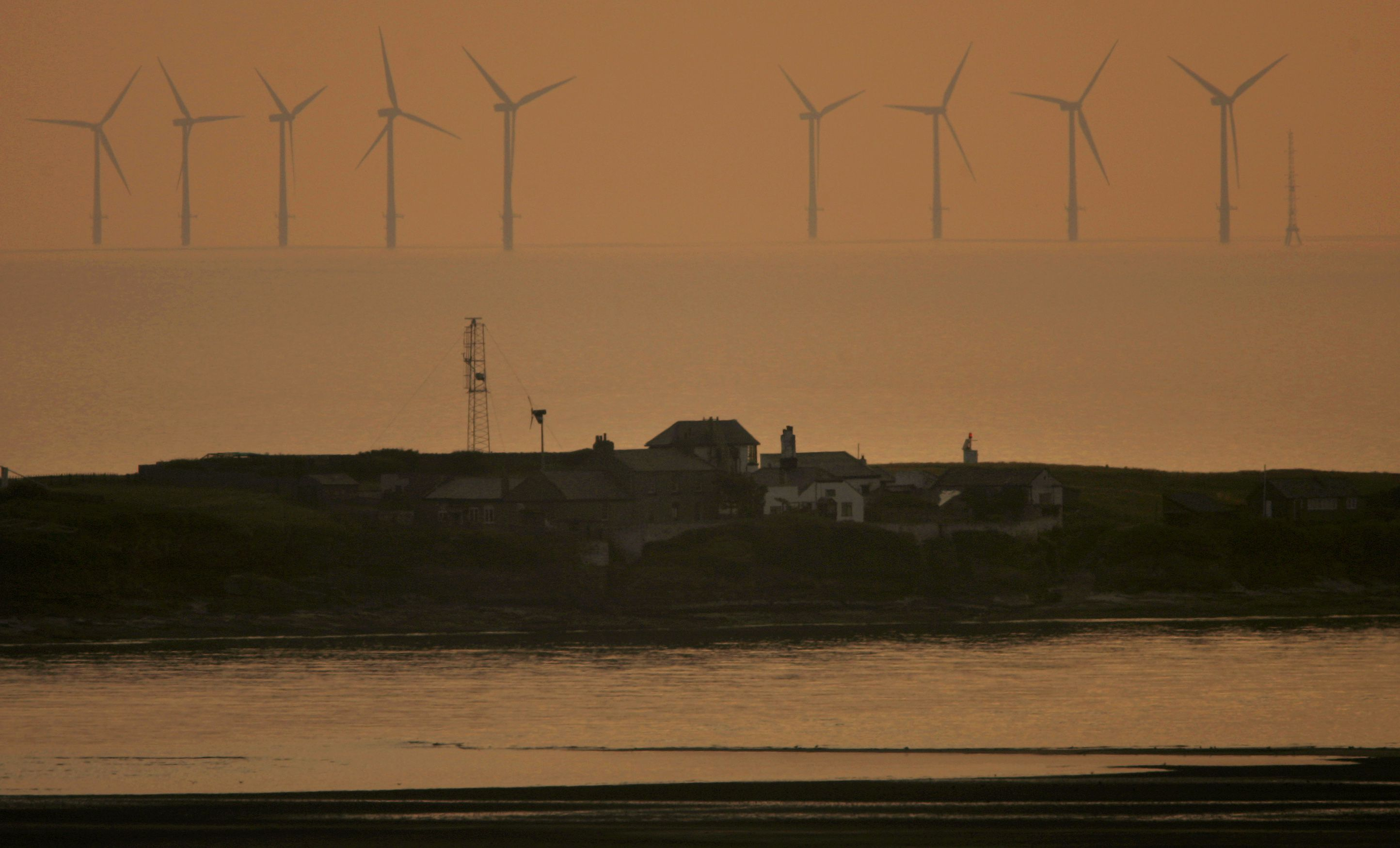 The sun sets behind the North Hoyle offshore wind farm in the Irish sea off the coast of northwest England, July 22, 2006. REUTERS/Phil Noble (BRITAIN) - RTR1FQUZ