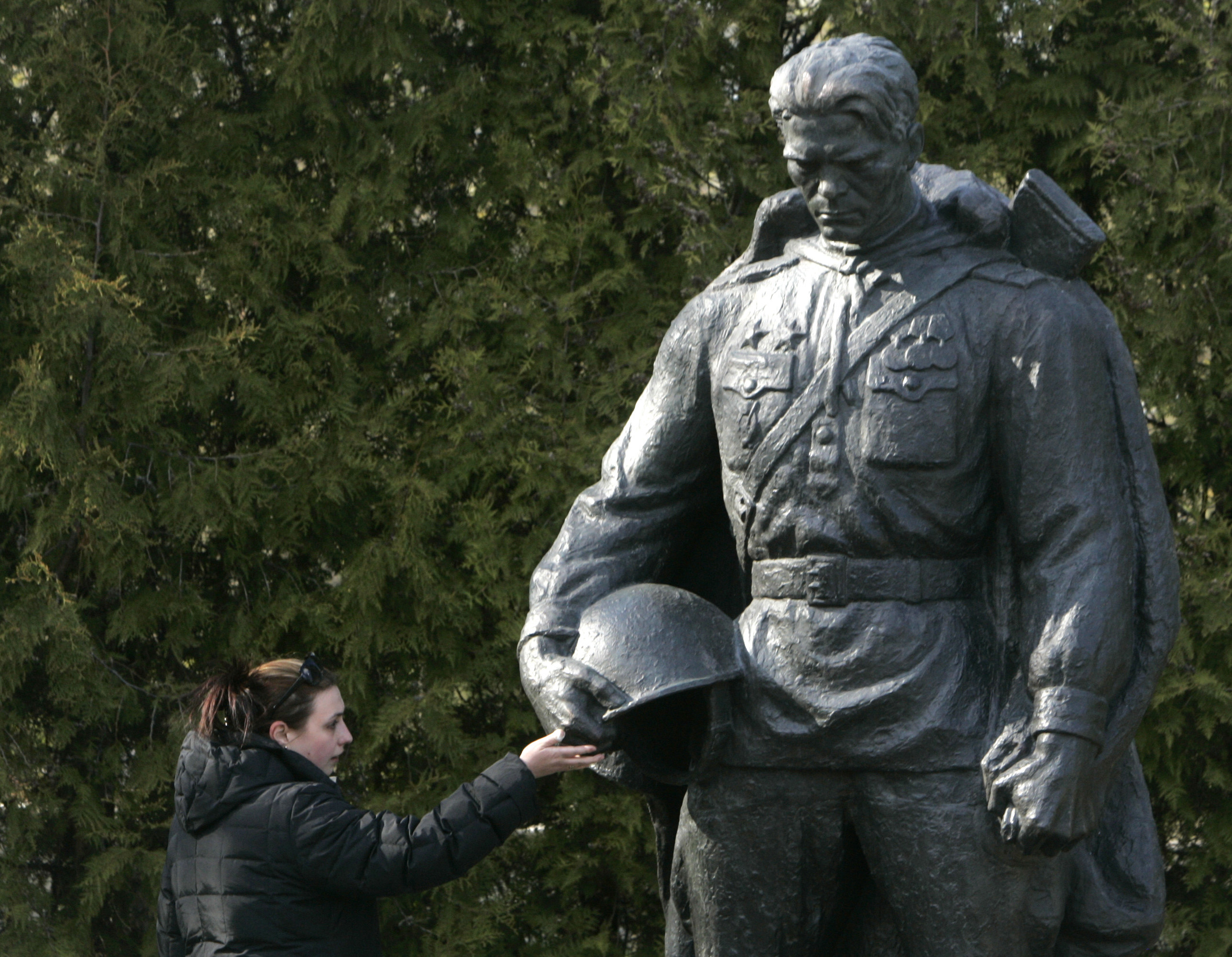 A woman touches a bronze statue of a World War Two Red Army soldier that was relocated from the city centre to a military cemetery in Tallinn April 30, 2007. Estonia put up the disputed Soviet Army monument in its new location on Monday after moving it last week from the centre of the capital amid riots by mainly Russian-speaking protesters. Tensions between the small Baltic state and Russia remained over the monument and Estonia protested over Russian inaction to stop demonstrations at its embassy in Moscow. Russia has called moving the statue from the centre of Tallinn an insult to those who fought against fascism. REUTERS/Ints Kalnins (ESTONIA) - RTR1P71A