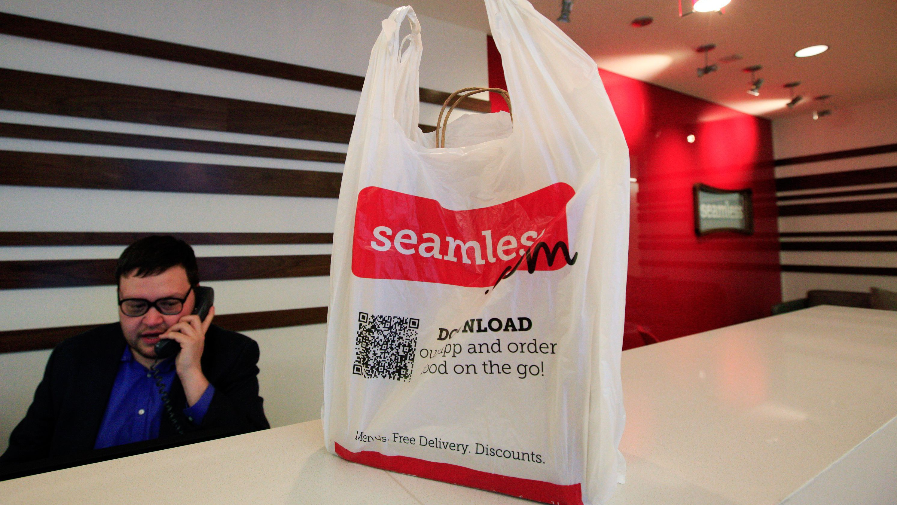 A man speaks on the phone next to a take-out bag at the reception desk at the offices of Seamless in New York January 10, 2012. Online delivery service Seamless is partnered with restaurants in over 30 major cities across the U.S. and Britain.  REUTERS/Brendan McDermid (UNITED STATES - Tags: BUSINESS FOOD) DRINK) - RTR2W4SO