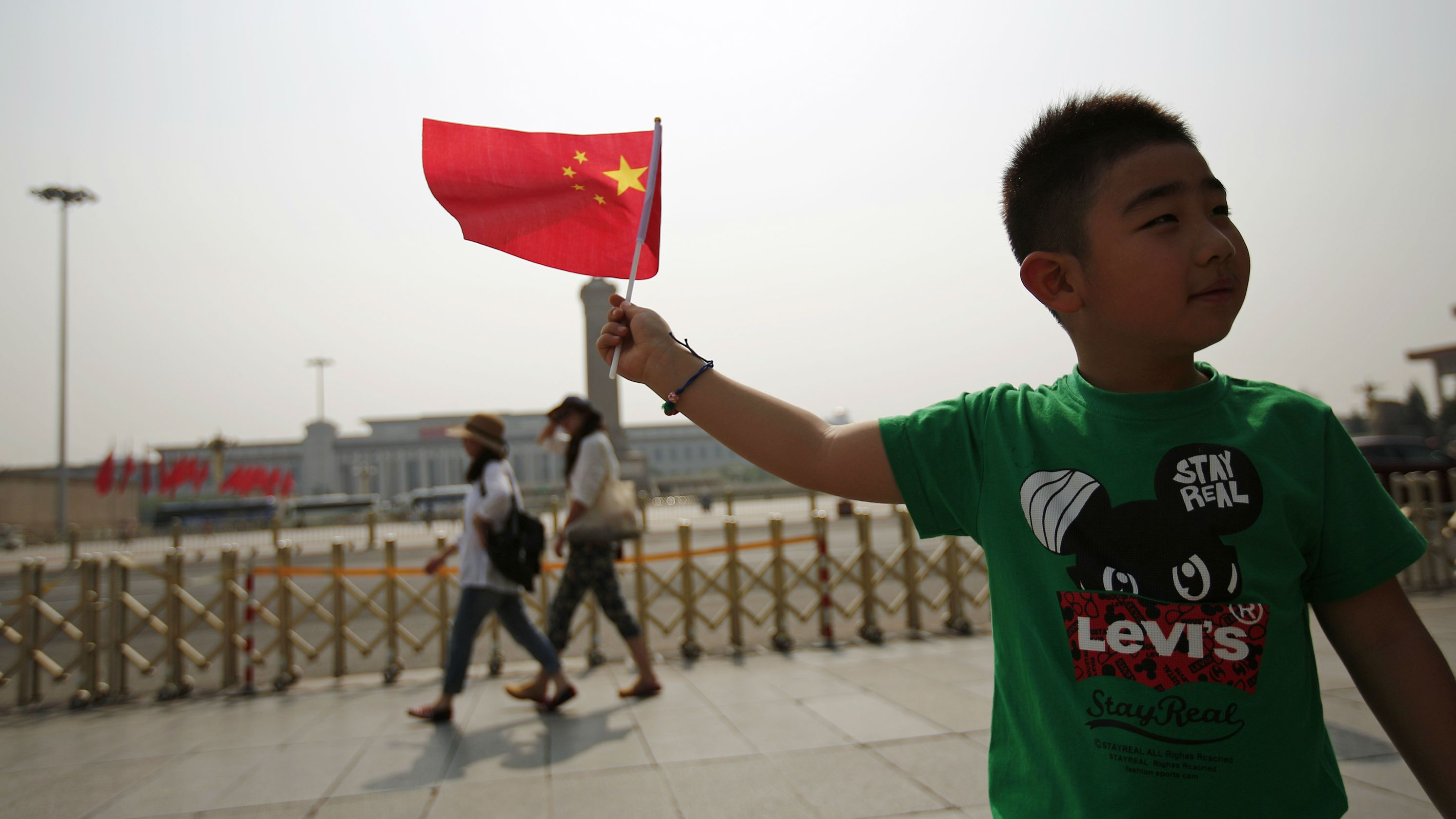A boy poses with a Chinese national flag in front of Tiananmen Square in Beijing June 4, 2014. From keeping foreign reporters off Beijing's Tiananmen Square to widespread censorship of the Internet, China marked 25 years since the bloody suppression of pro-democracy protests on Wednesday under a cloak of security. REUTERS/Kim Kyung-Hoon (CHINA - Tags: POLITICS TRAVEL CIVIL UNREST ANNIVERSARY)