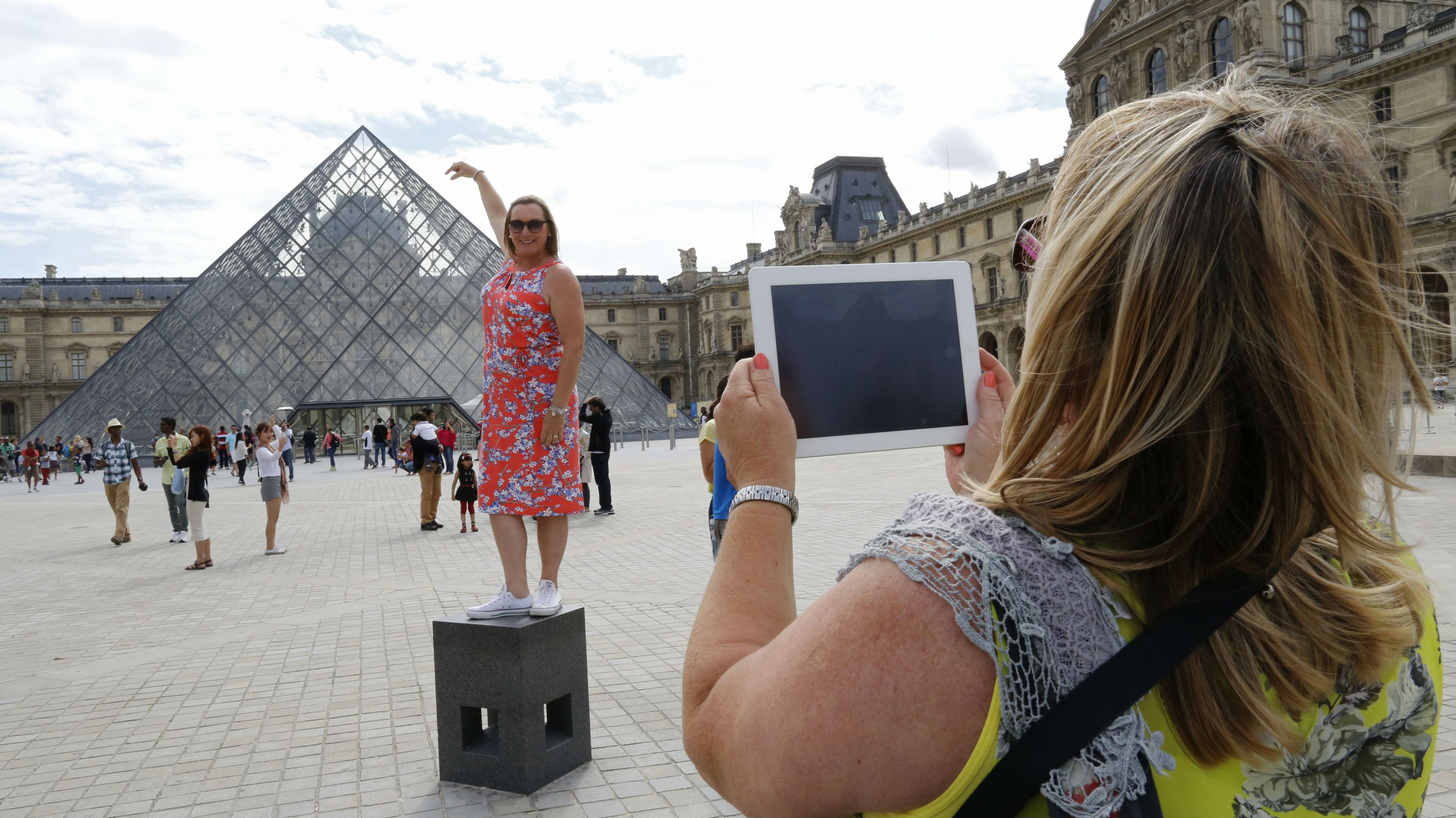 A tourist poses for a souvenir picture near the Pyramid of the Louvre Museum in Paris, August 12, 2014. France kept its title as the world's top tourist destination in 2013, drawing nearly 85 million visitors despite a lacklustre economic situation as Chinese interest intensified and North Americans surged back to the country. With its Mediterranean beaches and skiable mountain ranges, rich architectural heritage and tourist attractions France grew even more popular last year, welcoming 2 percent more visitors than in 2012. REUTERS/Jacky Naegelen (FRANCE - Tags: TRAVEL BUSINESS)