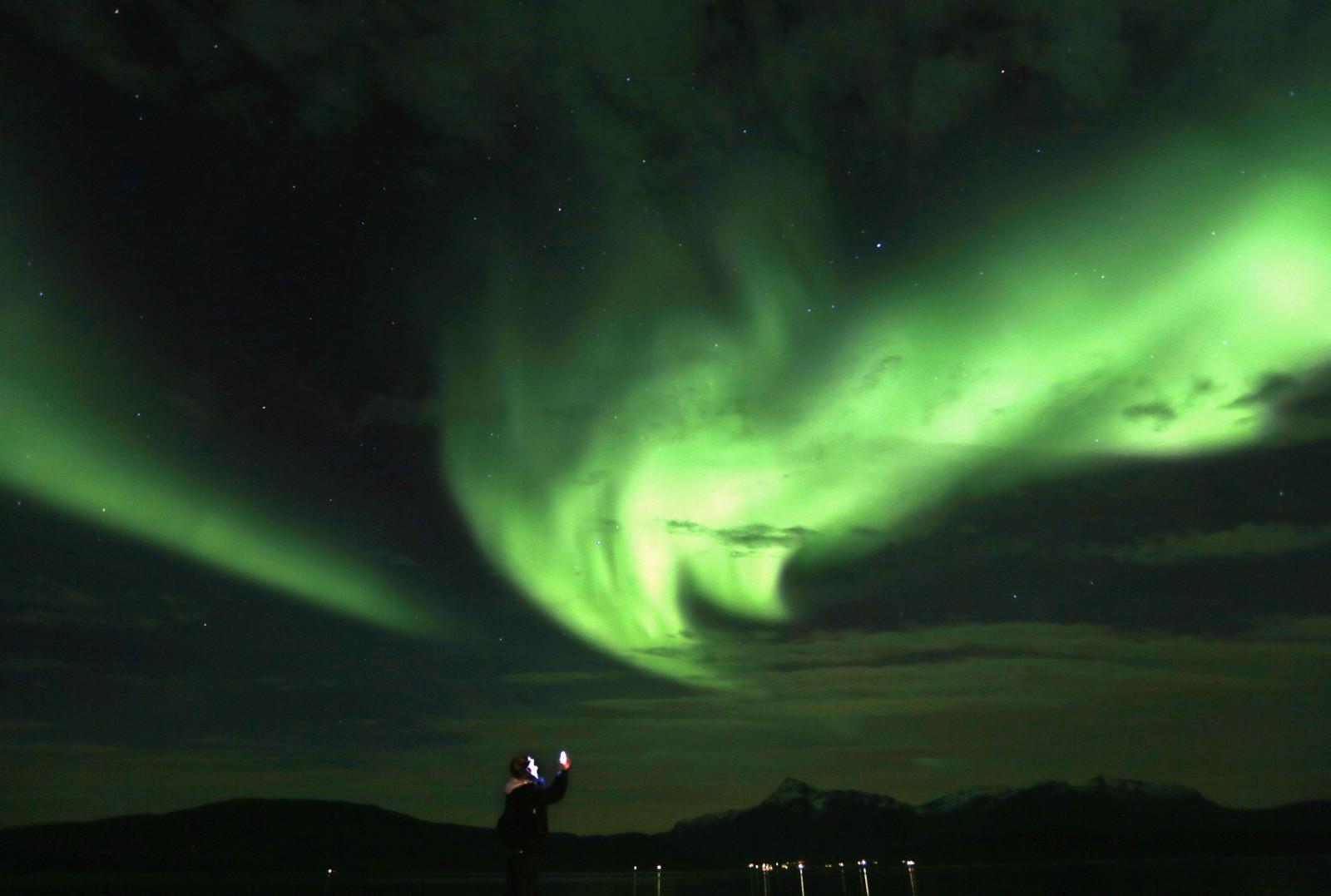 A tourist takes photos of an Aurora Borealis