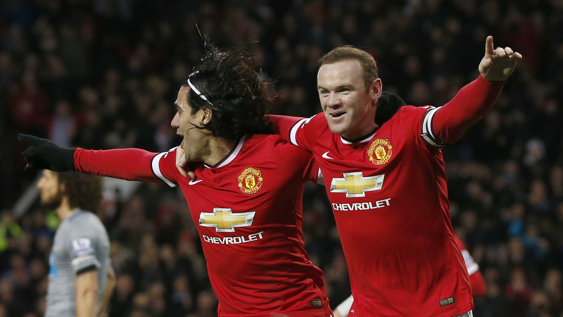 Manchester United's Wayne Rooney (R) celebrates after scoring a goal against Newcastle with team-mate Radamel Falcao during their English Premier League soccer match at Old Trafford in Manchester.