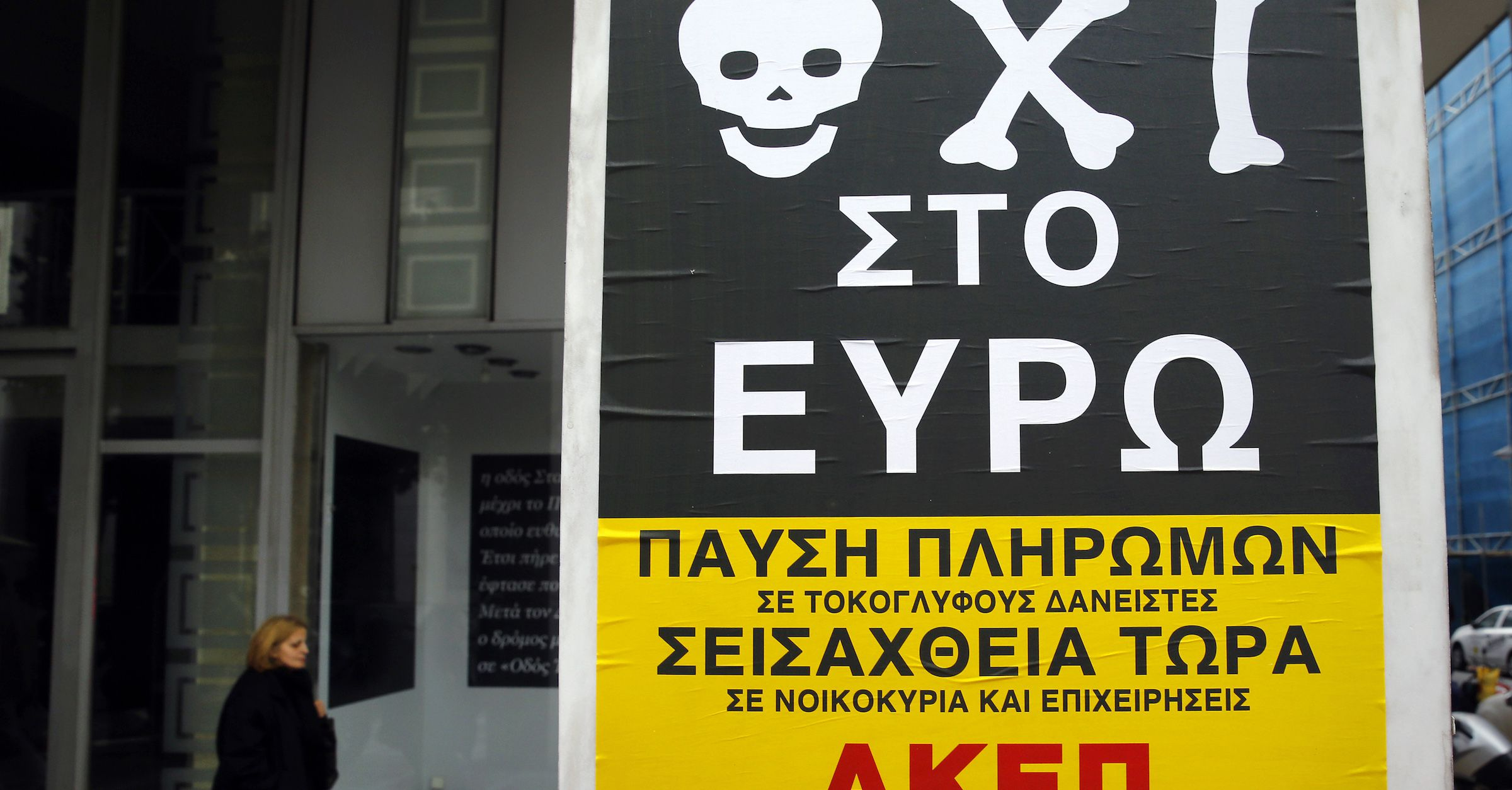 """A pedestrian walks by a poster that reads """"No to Euro"""" in central Athens, February 2, 2015. Greece's new left-wing government will not take any actions that would hurt the share values of the country's banks and does not plan to appoint party officials at key management posts, the government's spokesman said on Monday.  REUTERS/Yannis Behrakis (GREECE - Tags: POLITICS BUSINESS) - RTR4NW7W"""