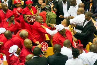 Members of Julius Malema's Economic Freedom Fighters (EFF) (in red) clash with security