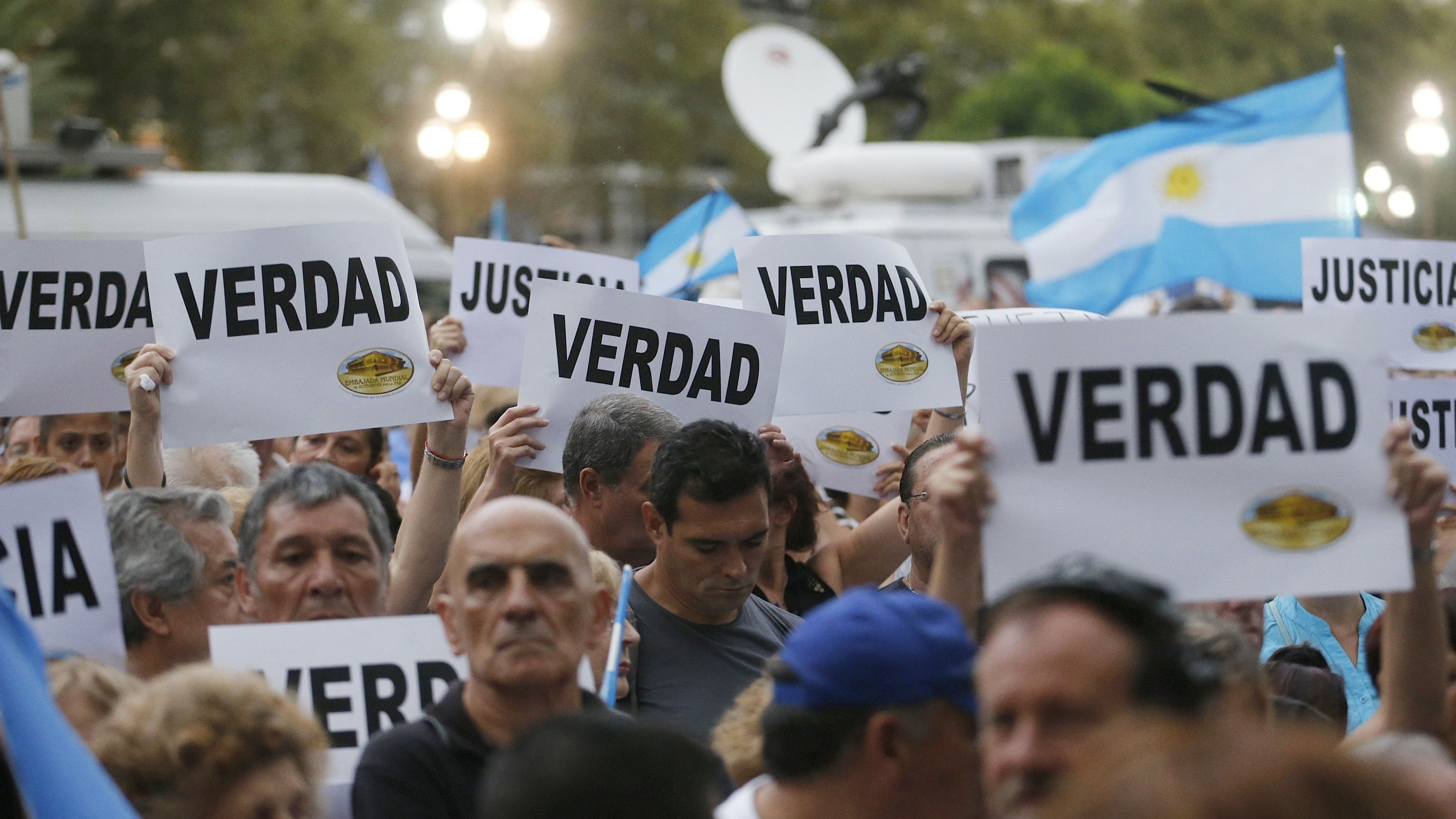 """Protesters hold up signs that read """"Truth"""" during a silent march to honour late state investigator Alberto Nisman in Buenos Aires February 18, 2015. Tens of thousands of Argentines are expected to march in silence through Argentina's capital, Buenos Aires, on Wednesday evening to honour Alberto Nisman, a state investigator who was poised to detail evidence behind his accusations that Argentine President Cristina Fernandez plotted to cover up his investigation into a 1994 bombing. Nisman was found dead with a single bullet to the head on January 18. REUTERS/Enrique Marcarian (ARGENTINA - Tags: POLITICS CIVIL UNREST CRIME LAW) - RTR4Q5XU"""