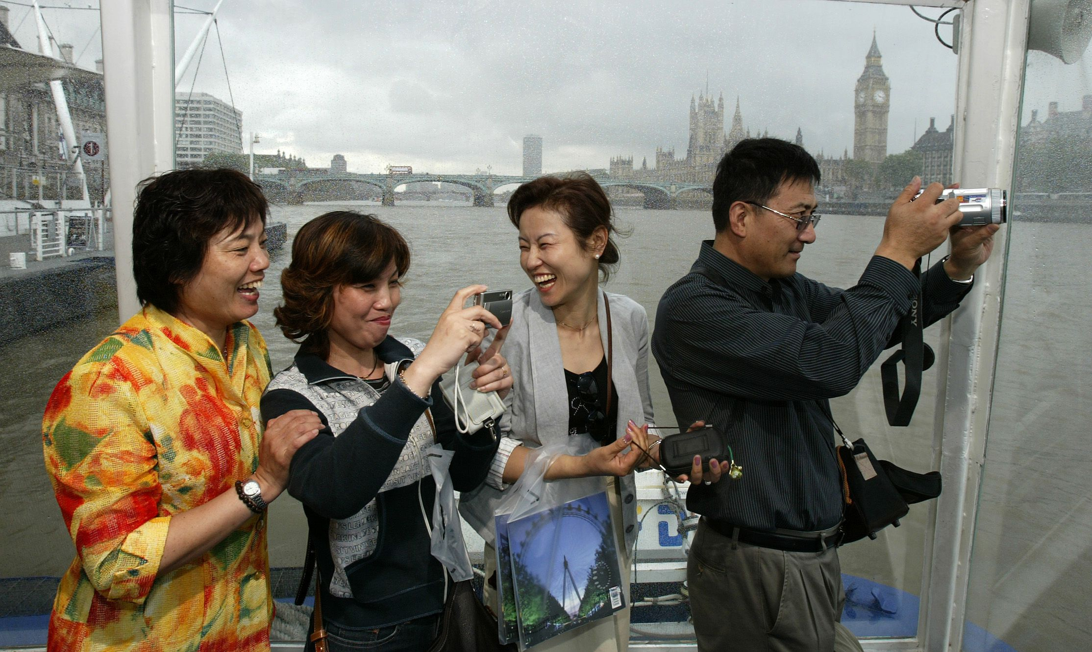 Mainland Chinese tourists take pictures during a cruise on the River Thames, central London, July 25, 2005.