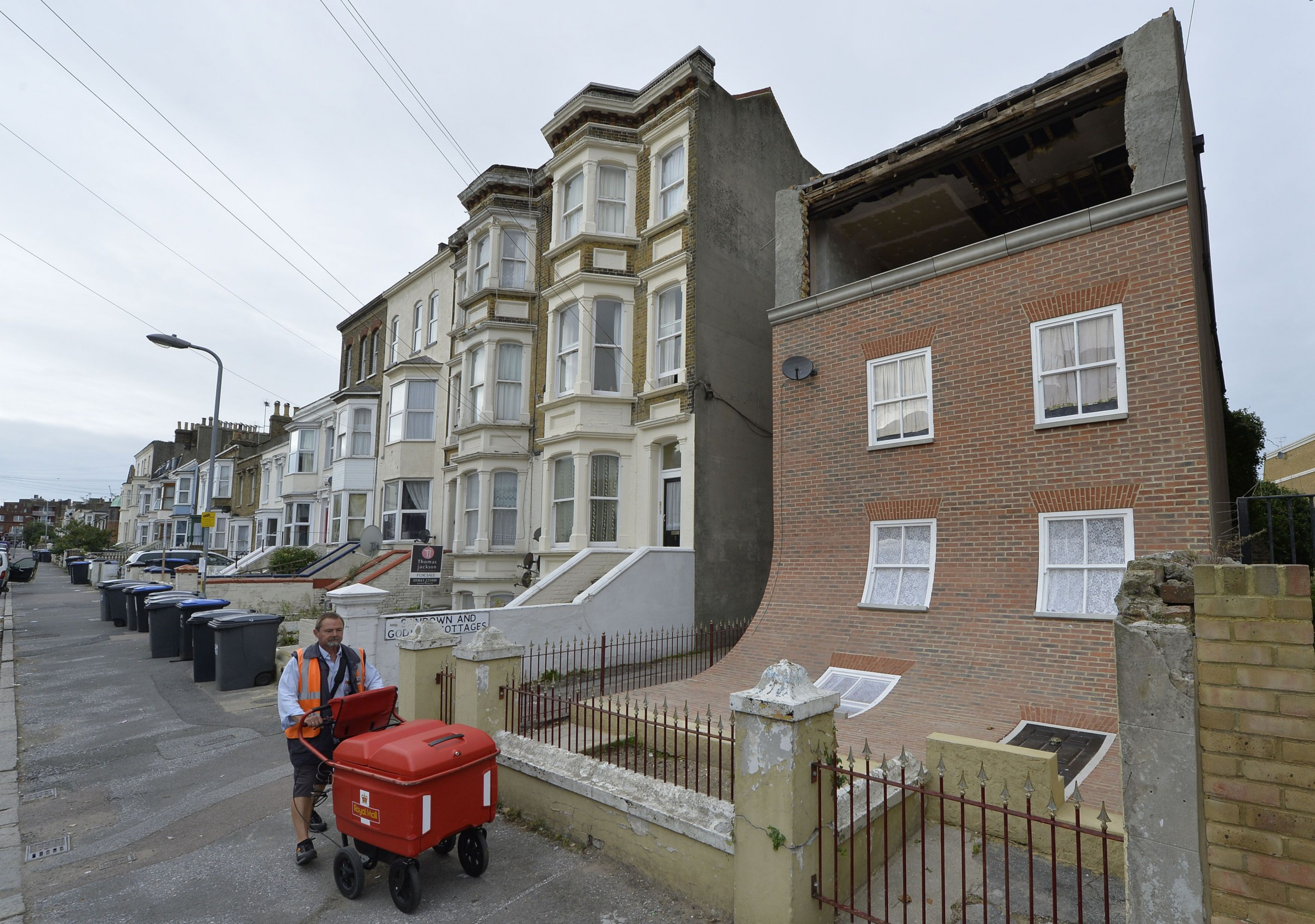 Postal worker Glenn Gray passes a piece of public art, depicting a sliding house in a residential road in Margate, southern England October 9, 2013.