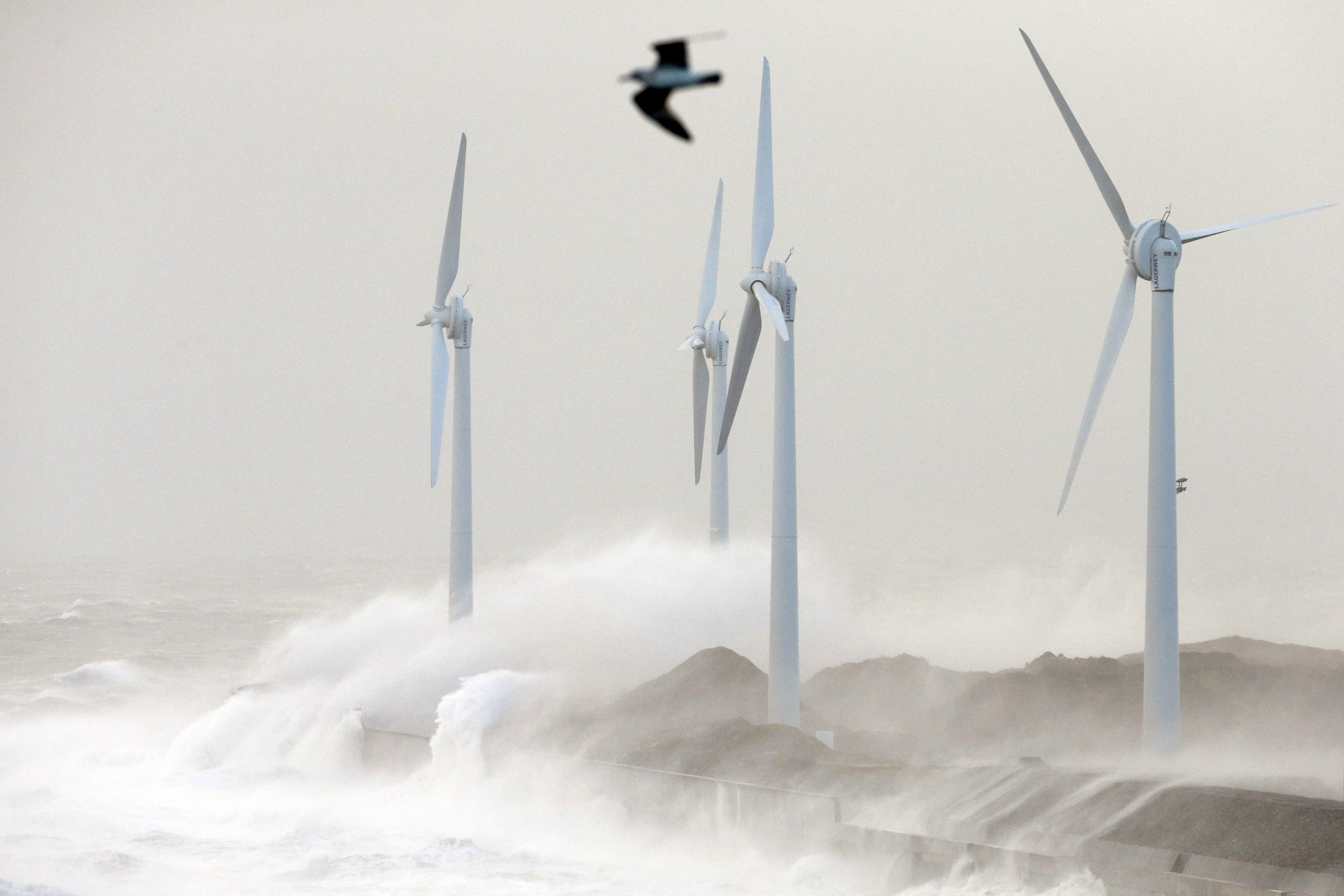 Waves crash against wind turbines during a storm named Christian that battered France at Boulogne sur Mer, northern France, October 28, 2013.