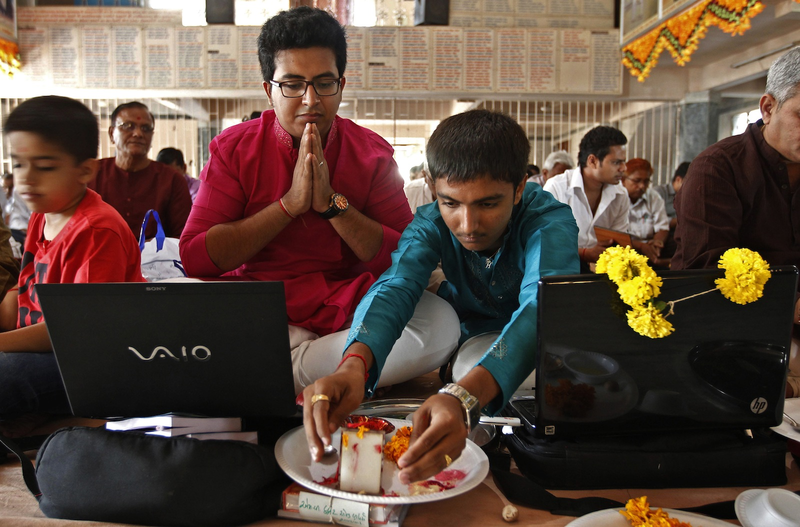 Businessmen offer prayers to Hindu gods in front of their laptops as part of a ritual to worship the Hindu deity of wealth Goddess Lakshmi on Diwali, the Indian festival of lights, in the western Indian city of Ahmedabad.