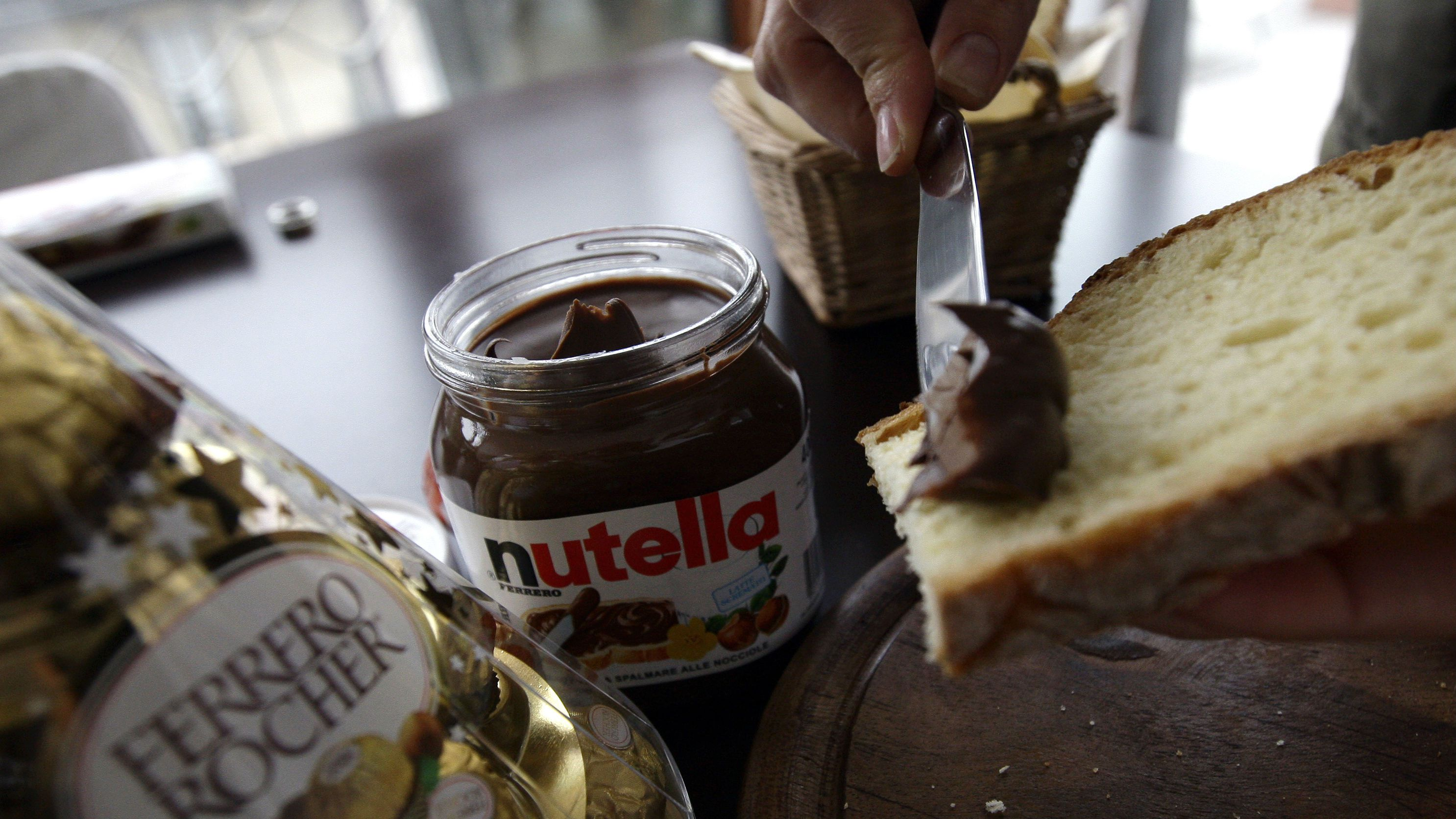 A woman spreads Nutella on a slice of bread in Milan November 20, 2009. Cadbury suitors Ferrero and Hershey would likely break the UK confectioner up into separate businesses if a mooted bid for the company succeeds, an Italian newspaper reported. Italian chocolate maker Ferrero and U.S.-based Hershey said on Wednesday they were reviewing a possible offer for Cadbury, which is the subject of a hostile 9.9 billion pound ($16.5 billion) bid by U.S. food group Kraft. Unlisted Ferrero is mainly interested in Cadbury's gum and candy division, a unit worth about 5 billion euros ($7.4 billion), business daily Il Sole 24 Ore said on Friday. REUTERS/Stefano Rellandini (ITALY BUSINESS FOOD)