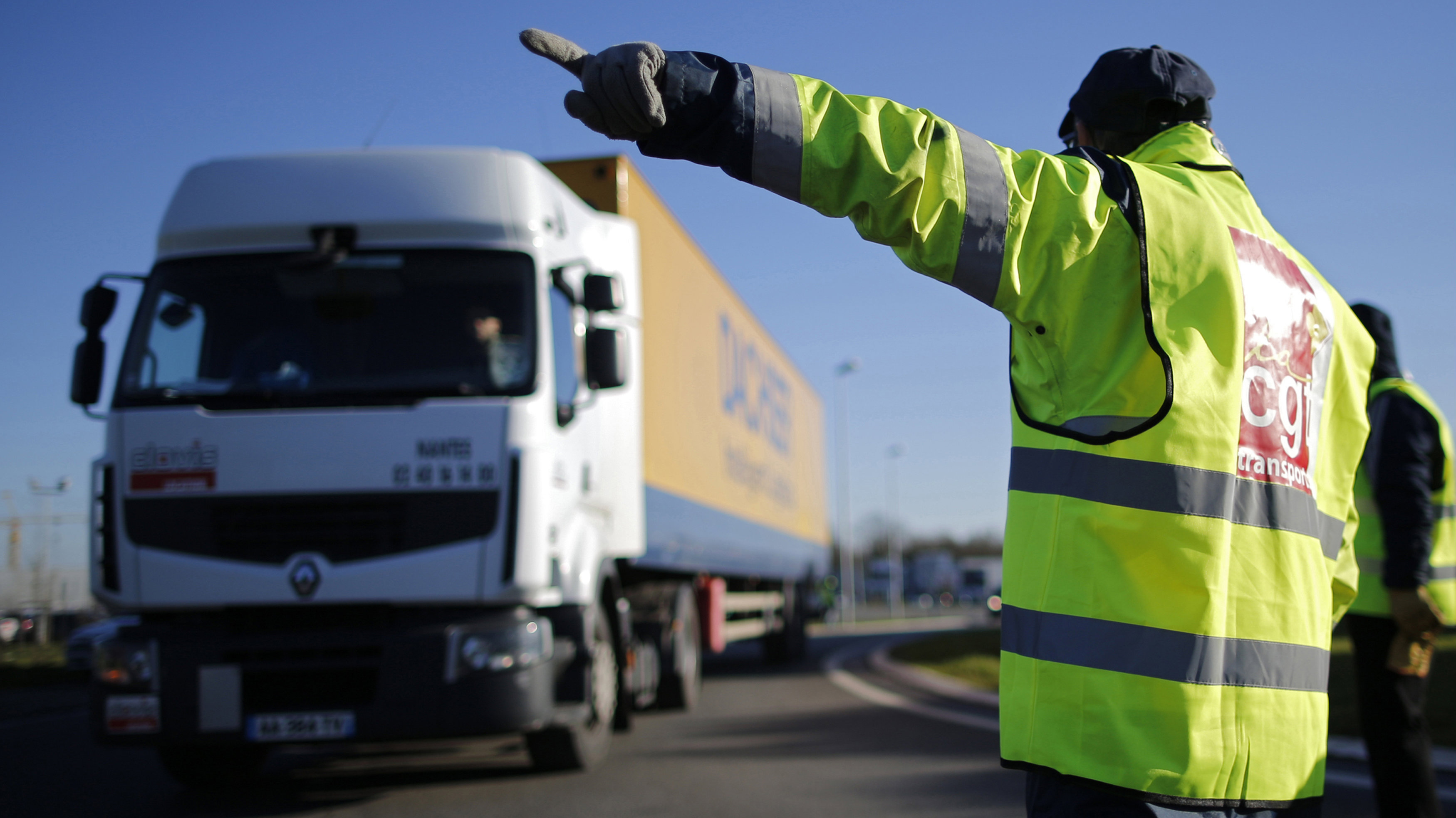 A truck driver wears a vest with a labour union logo as truckers stage a blockade in Carquefou near Nantes January 19, 2015. French truck drivers staged go-slow operations on highways with lorry blockades during a strike against salaries and working conditions.