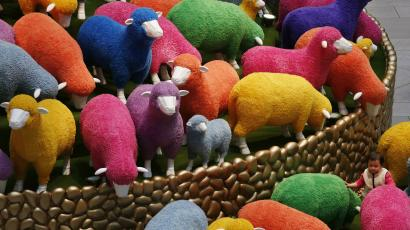 A toddler stands in a Lunar New Year display featuring sheep at a shopping mall in Hong Kong.