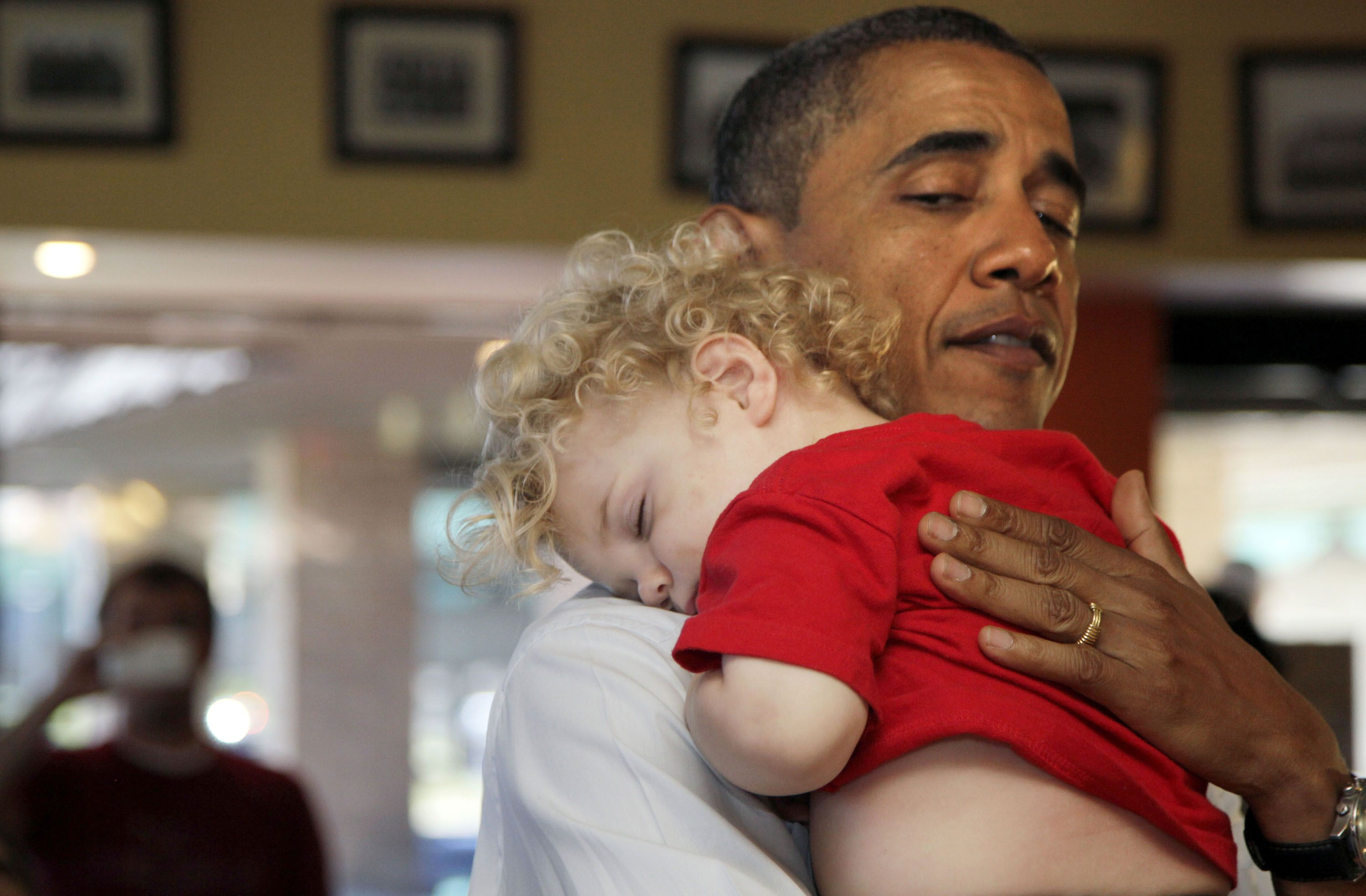 President Barack Obama holds a sleeping baby boy as he visits Ross' restaurant in Bettendorf, Iowa, Tuesday, June 28, 2011. (AP Photo/Carolyn Kaster)