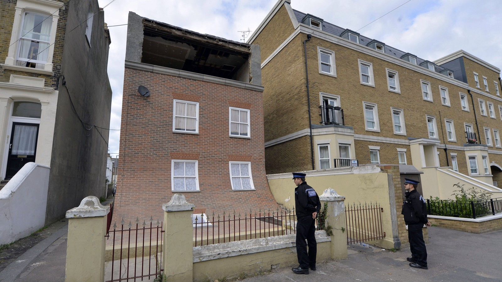 Two police community support officers look at a piece of public art, depicting a sliding house in a residential road in Margate, southern England October 9, 2013. The sculpture, entitled 'From the Knees of my Nose to the Belly of my Toes' was created by London-based artist Alex Chinneck, and will stand for a year. It was built using a Victorian house in the seaside town which was compulsorily purchased by the region's council after lying empty for eleven years.