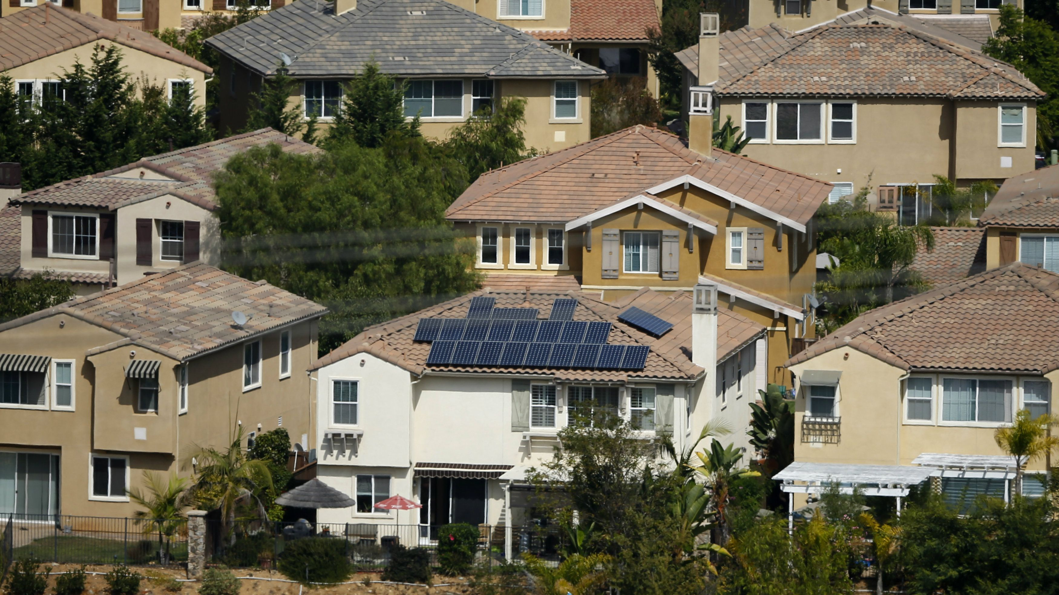 A home with solar panels on its roof is shown in a residential neighborhood in San Marcos, California