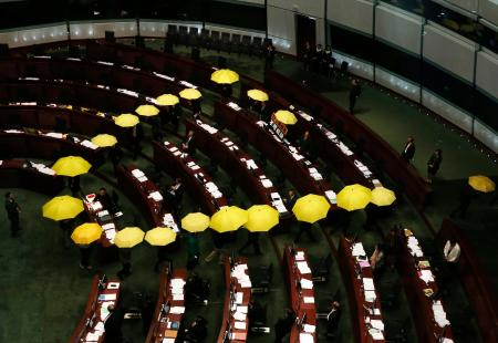 Pro-democracy lawmakers carrying yellow umbrellas, symbols for the Occupy Central movement, leave in the middle of a Legislative Council meeting as a gesture to boycott the government in Hong Kong