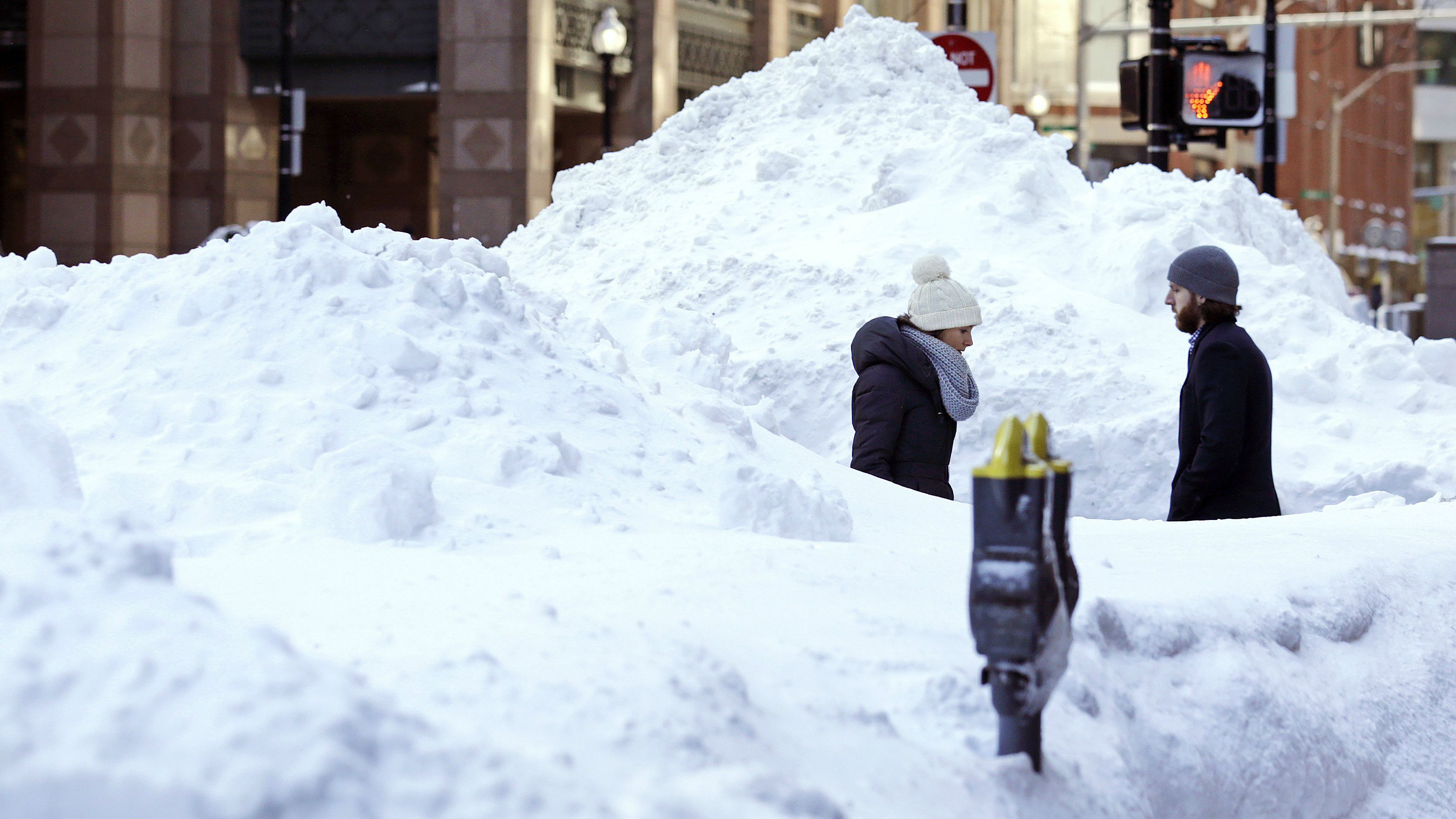Pedestrians maneuver around huge snow piles as they walk through the Financial District of Boston, Tuesday, Feb. 3, 2015. The Boston area has received about 40 inches of snow in the past week. (AP Photo/Charles Krupa)