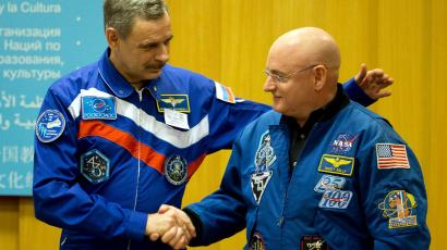 NASA astronaut Scott Kelly (R) shakes hands with Russian cosmonaut Mikhail Korniyenko after a news conference to preview the upcoming year-long expedition and to discuss the future of the International laboratory at the UNESCO Headquarters in Paris December 18, 2014. Kelly and Korniyenko are scheduled to blast off to the International Space Station (ISS) in March 2015 to begin a year?s stay aboard the orbiting laboratory. This will be the longest time astronauts have spent on the Station on a single mission.