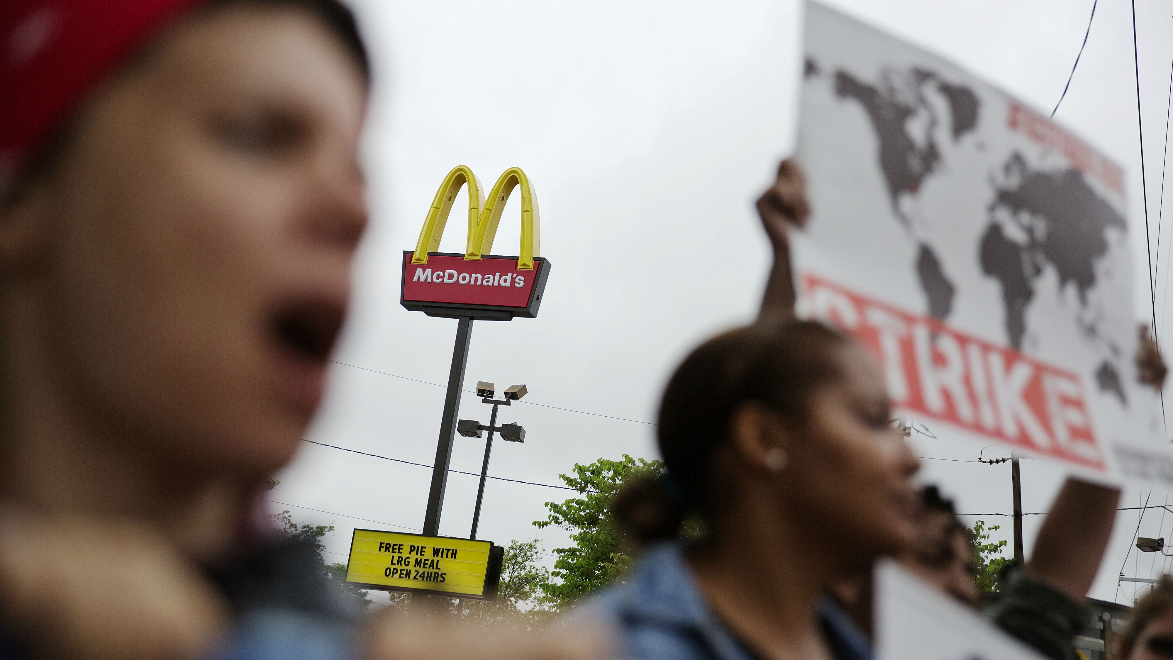 Demonstrators protest outside a McDonald's restaurant demanding better wages, Thursday, May 15, 2014, in Atlanta. Calling for higher pay and the right to form a union without retaliation, fast-food chain workers in Atlanta protested Thursday as part of a wave of strikes and protests in 150 cities across the U.S. and 33 additional countries on six continents. (AP Photo/David Goldman)