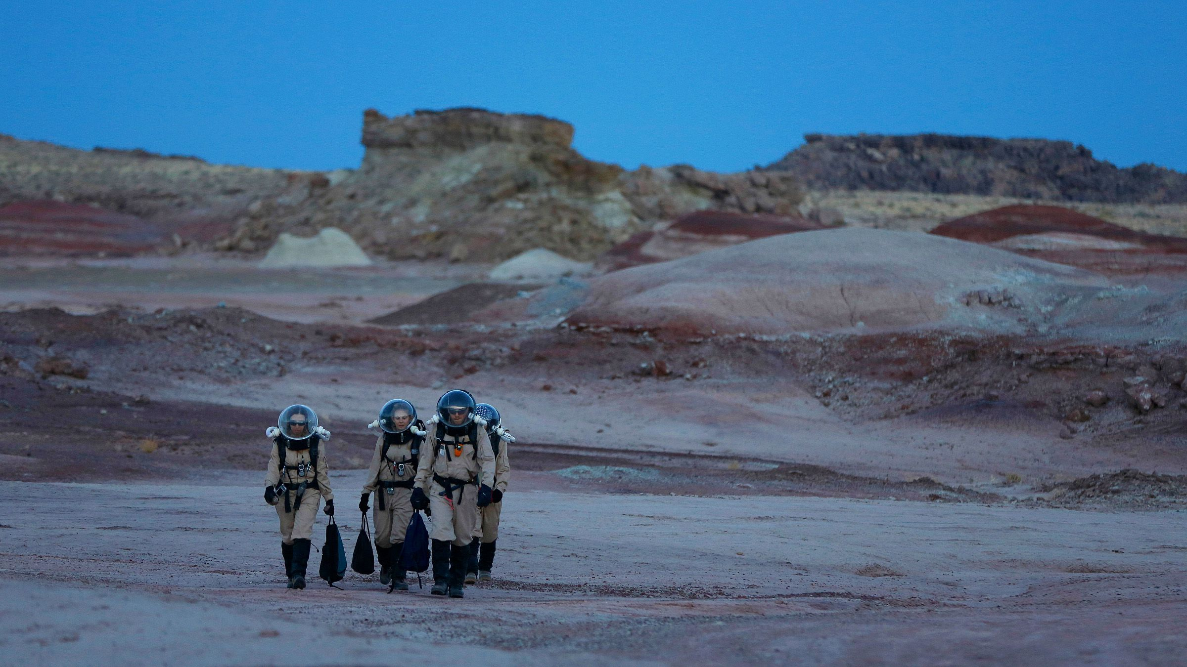 Members of Crew 125 EuroMoonMars B mission return after collecting geologic samples for study at the Mars Desert Research Station (MDRS) in the Utah desert March 2, 2013. The MDRS aims to investigate the feasibility of a human exploration of Mars and uses the Utah desert's Mars-like terrain to simulate working conditions on the red planet. Scientists, students and enthusiasts work together developing field tactics and studying the terrain. All outdoor exploration is done wearing simulated spacesuits and carrying air supply packs and crews live together in a small communication base with limited amounts of electricity, food, oxygen and water. Everything needed to survive must be produced, fixed and replaced on site. Picture taken March 2, 2013.