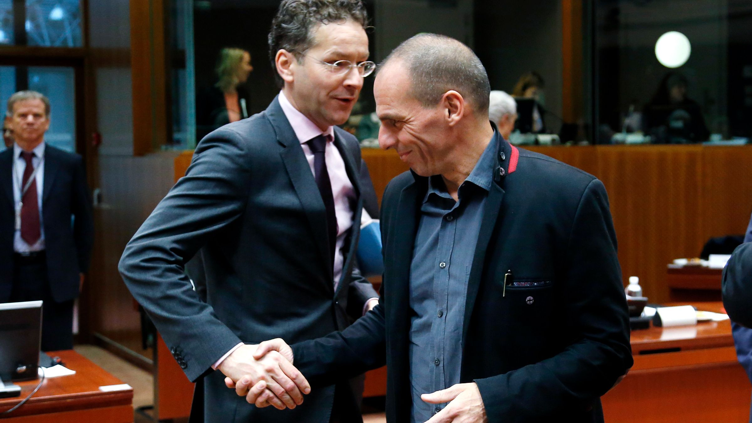 """Dutch Finance Minister and Eurogroup chairman Jeroen Dijsselbloem shakes hands with Greek Finance Minister Yanis Varoufakis (R) during an European Union finance ministers meeting in Brussels February 17, 2015. The European Union will continue working on Greece's debt problems to achieve """"a very good outcome"""" for average Europeans, Varoufakis said on Tuesday."""