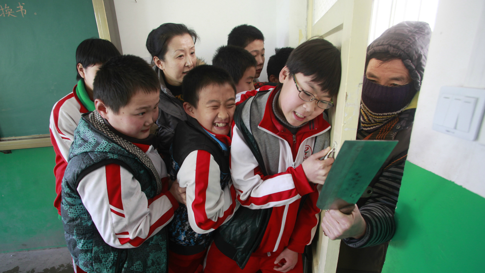 A teacher and her students try to shut a door against an intruder during an anti-violence exercise at a primary school in Jinan, Shandong province, December 18, 2012. The exercise was held four days after last Friday's knife attack at an primary school in Henan province, leaving more than 20 children and an elderly villager injured. Picture taken December 18, 2012. REUTERS/China Daily (CHINA - Tags: CRIME LAW EDUCATION) CHINA OUT. NO COMMERCIAL OR EDITORIAL SALES IN CHINA