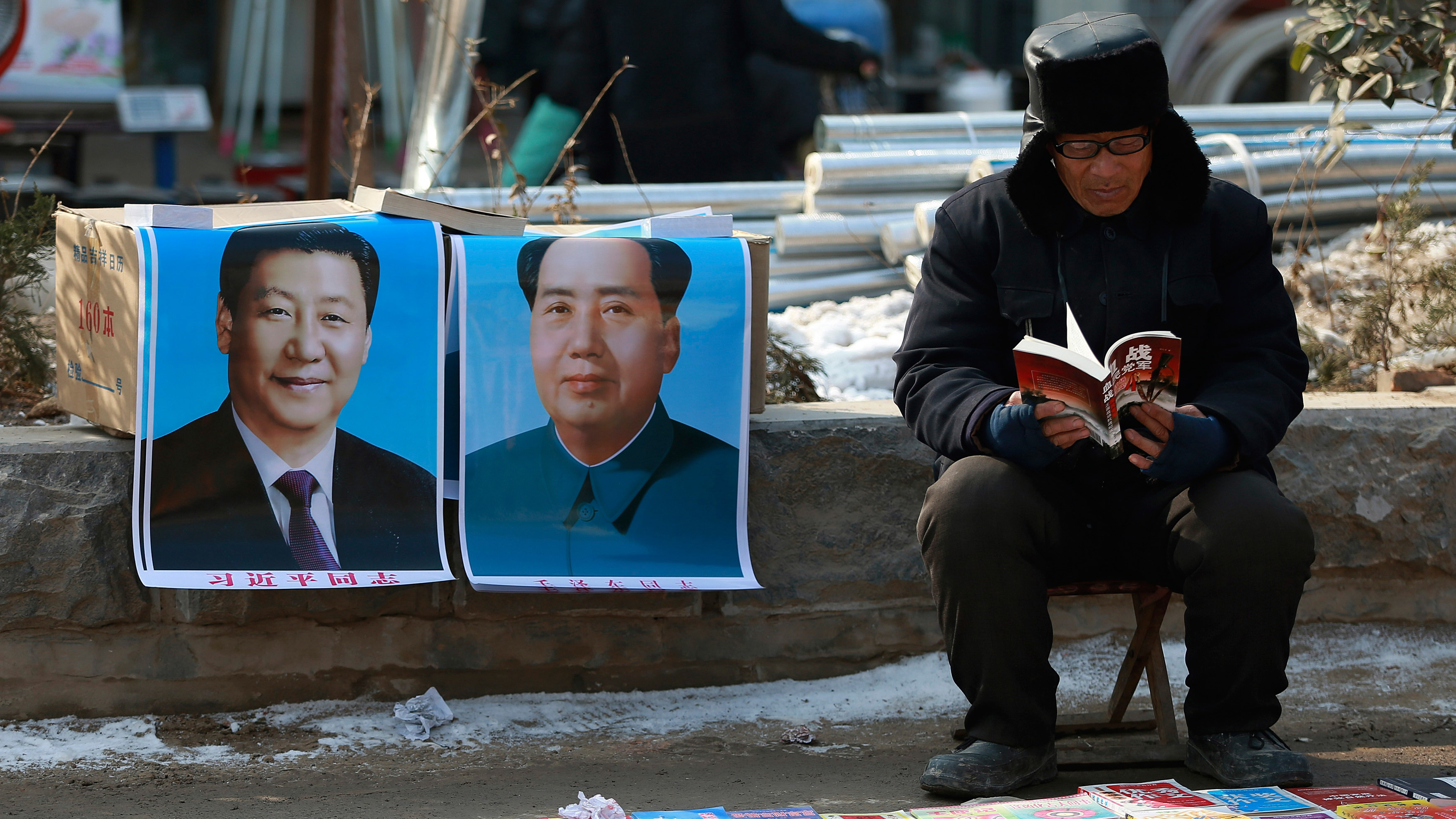 A book vendor reads a book as he waits for customer next to portraits of Chinese President Xi Jinping (L) and late Chairman Mao Zedong
