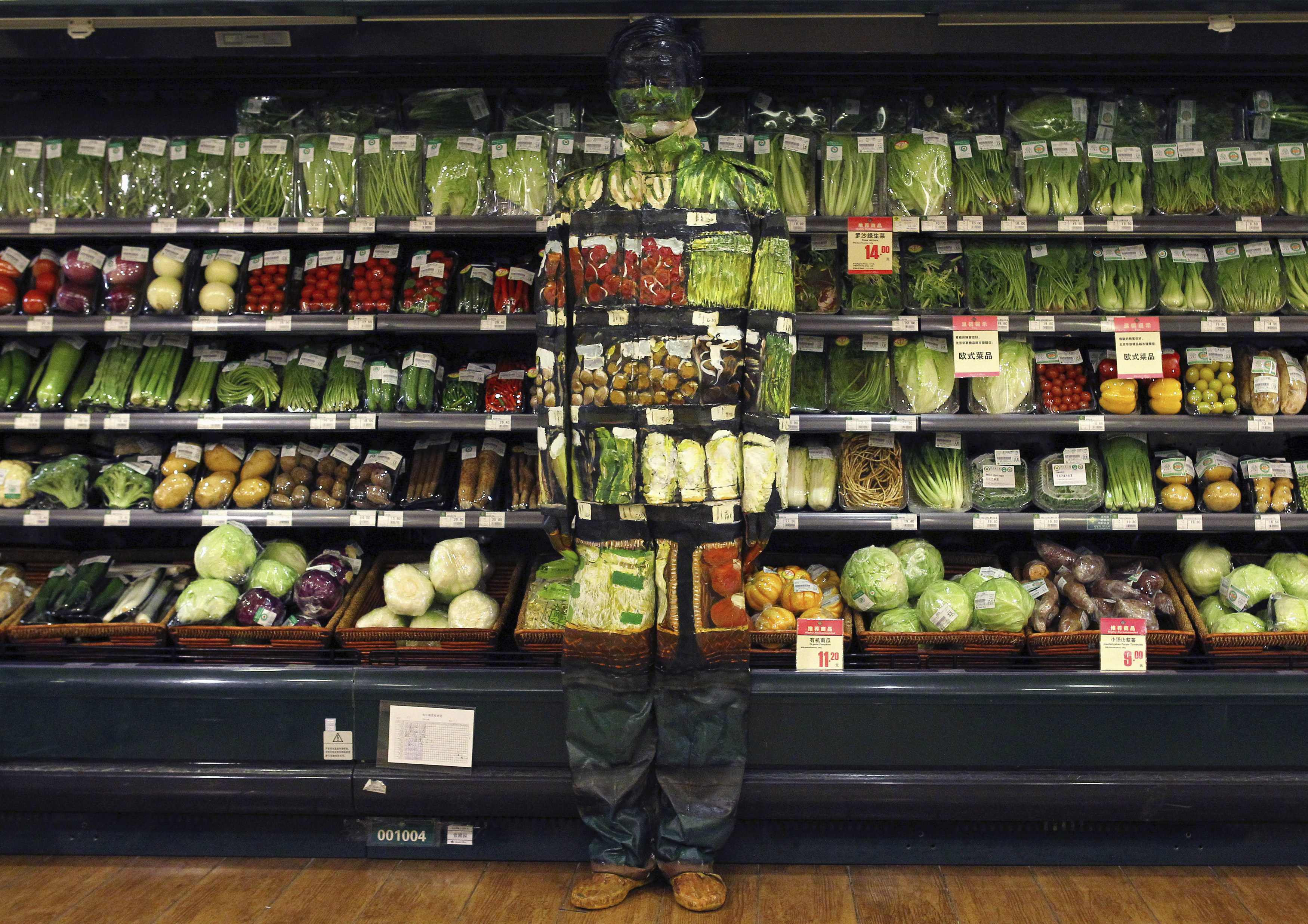 """Artist Liu Bolin demonstrates an art installation by blending in with vegetables displayed on the shelves at a supermarket in Beijing November 10, 2011. Liu, also known as the 'Vanishing Artist', started practising being """"invisible"""" by means of optical illusions more than six years ago. Picture taken November 10, 2011."""