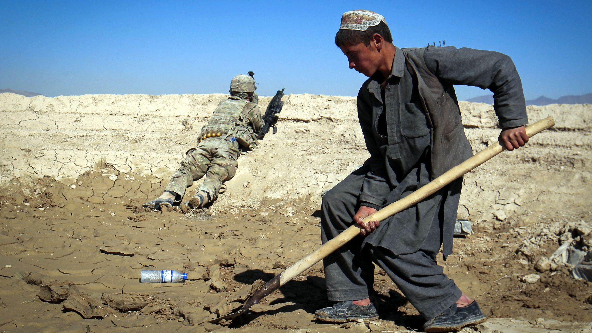 An Afghan boy works at a construction site as a U.S. Army soldier of 3/1 AD Task Force Bulldog takes position during a joint patrol with Afghan National Army (ANA) in a village in Kherwar district in Logar province, eastern Afghanistan, May 23, 2012.