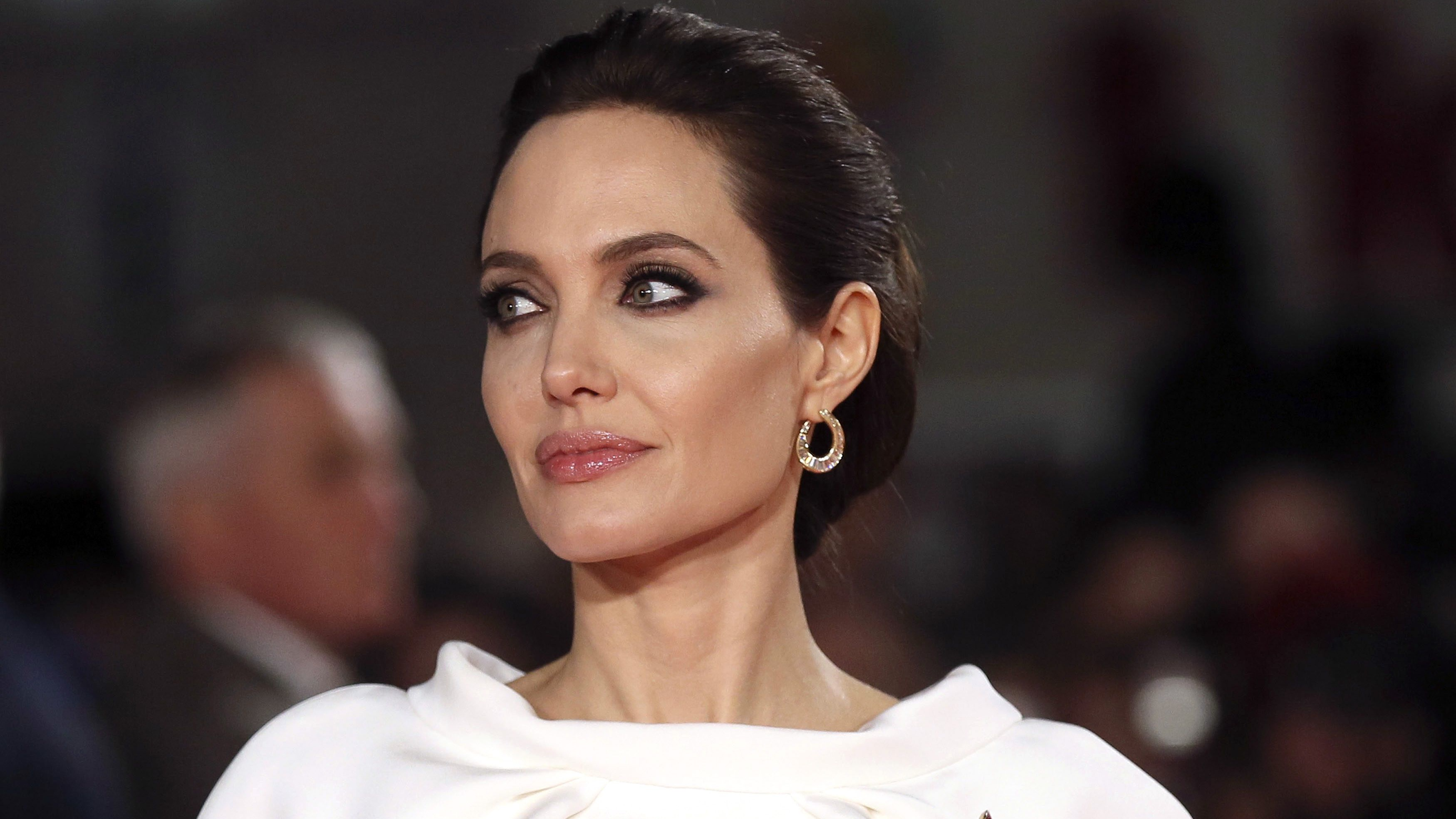 """Angelina Jolie poses for a photograph as she arrives for the UK premiere of """"Unbroken""""."""