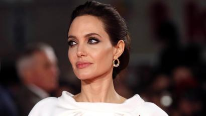 "Angelina Jolie poses for a photograph as she arrives for the UK premiere of ""Unbroken""."
