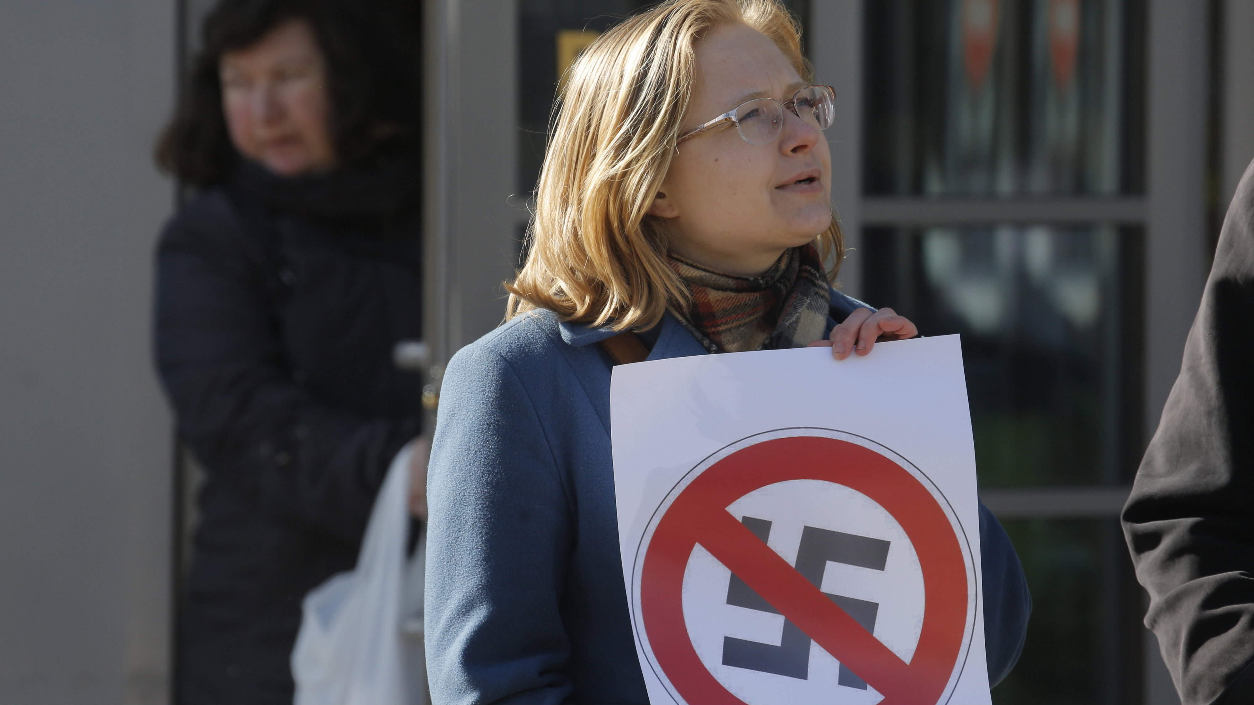A Russian anti-fascist activist holds a poster during a protest near the venue of the the International Russian Conservative Forum in St. Petersburg, Russia, Sunday, March 22, 2015. Nationalist supporters of Russian President Vladimir Putin brought together controversial far-right politicians from across Europe on Sunday in an effort to demonstrate international support for Russia and weaken European Union commitment to sanctions imposed on Russia over its role in Ukraine.