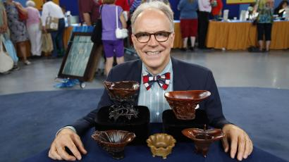 "In this Saturday, July 23, 2011 photo, Asian art expert and veteran ""Antiques Roadshow."" appraiser Lark Mason poses with a collection of Chinese rhinoceros horned cups in Tulsa, Okla. PBS says the collection was judged by Mason to be worth $1 million to $1.5 million, the most valuable item brought in for appraisal in the history of ""Antiques Roadshow,"" which will air its 16th season next year."