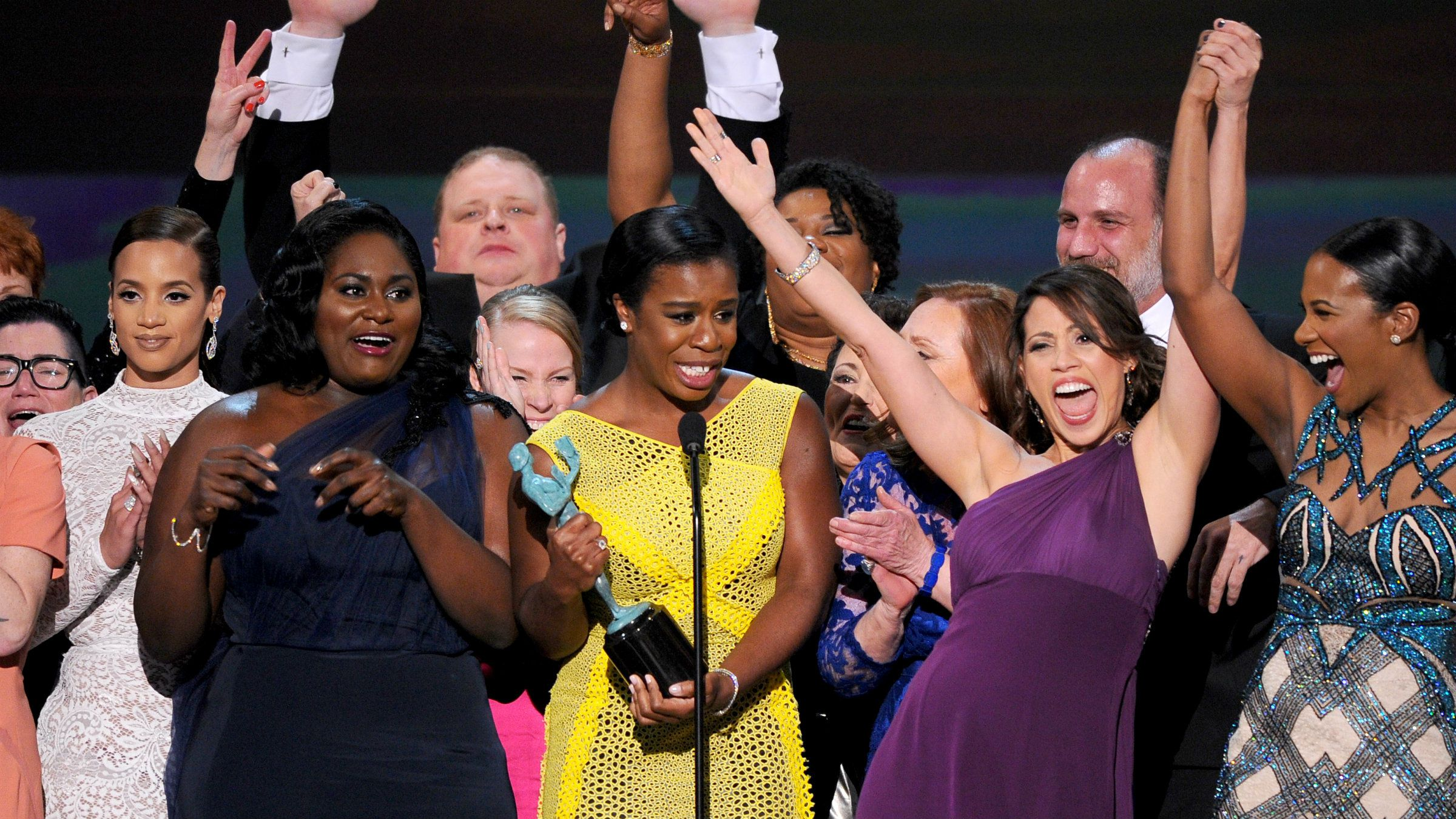 """Uzo Aduba, center, and the cast of """"Orange is the New Black"""" accept the award for outstanding ensemble in a comedy series on stage at the 21st annual Screen Actors Guild Awards at the Shrine Auditorium on Sunday, Jan. 25, 2015, in Los Angeles."""