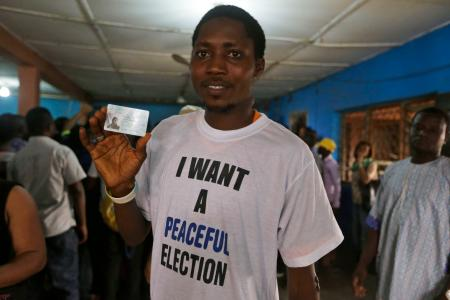 Man displays his voter's card and wears a t-shirt with the inscription ' i want a peaceful election '
