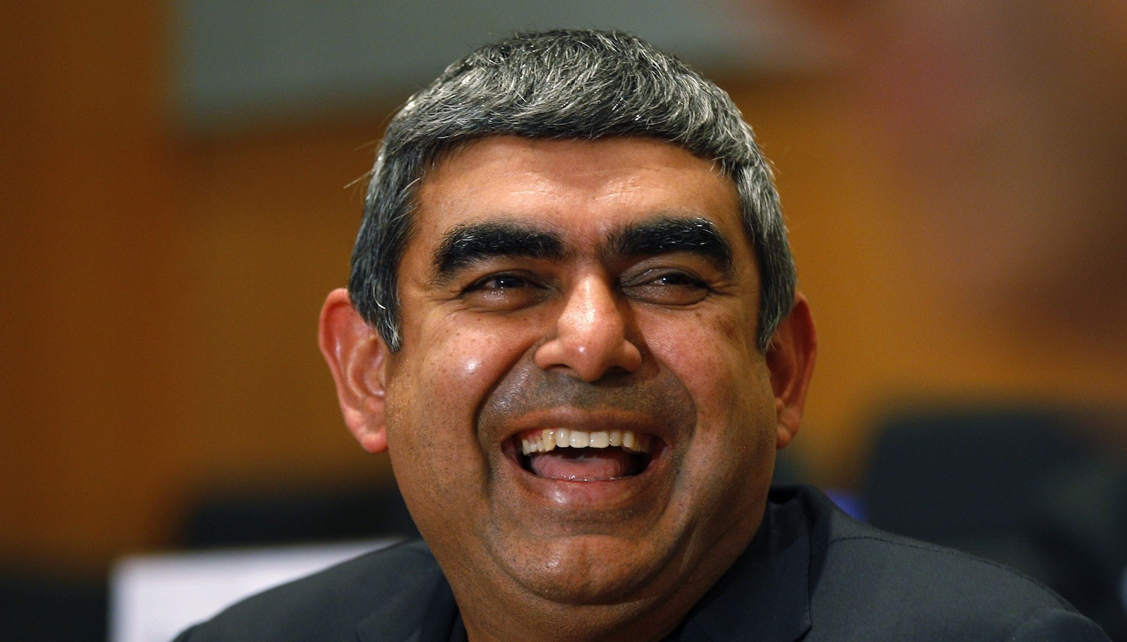 Infosys new Chief Executive Officer and Managing Director Vishal Sikka smiles during a press conference at the company's headquarters in Bangalore, India, Thursday, June 12, 2014.