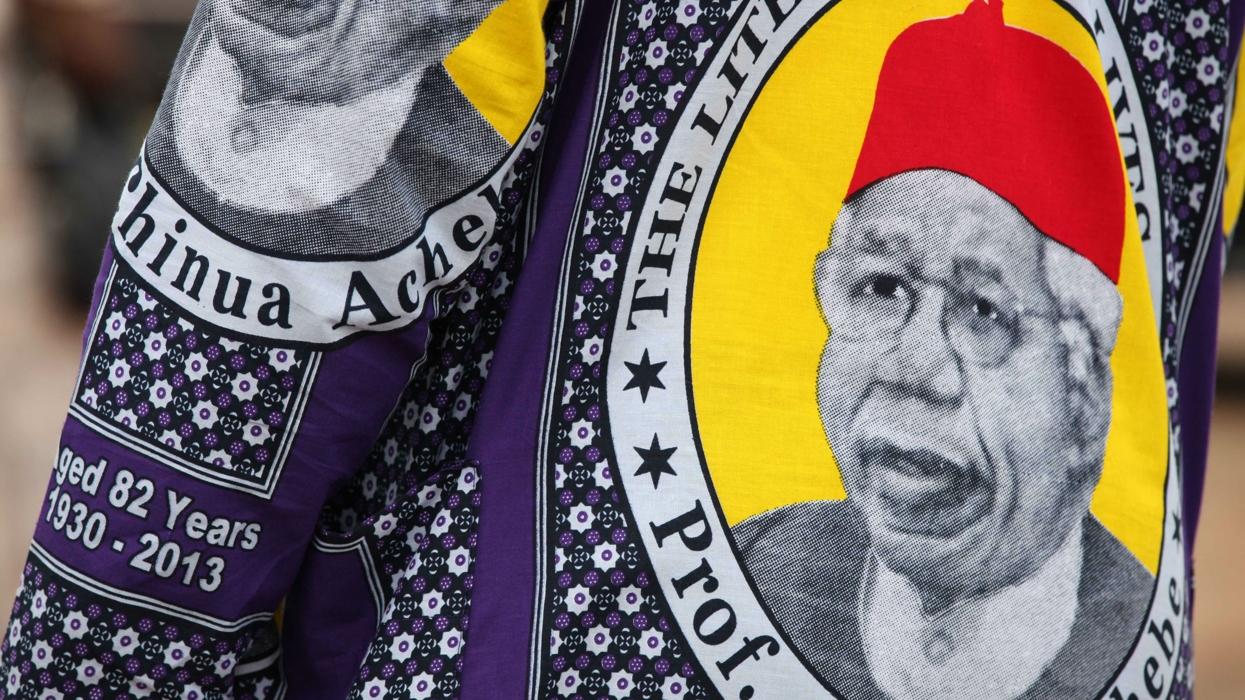 A man wears African print fabric bearing the image of with the face of the late author Chinua Achebe in Awka, Nigeria, Wednesday, May 22, 2013. People gathered Wednesday to celebrate the life of author Chinua Achebe, who died in March at the age of 82. His family plans to bury the literary icon Thursday in his home village of Ogidi. (AP Photo/Sunday Alamba)